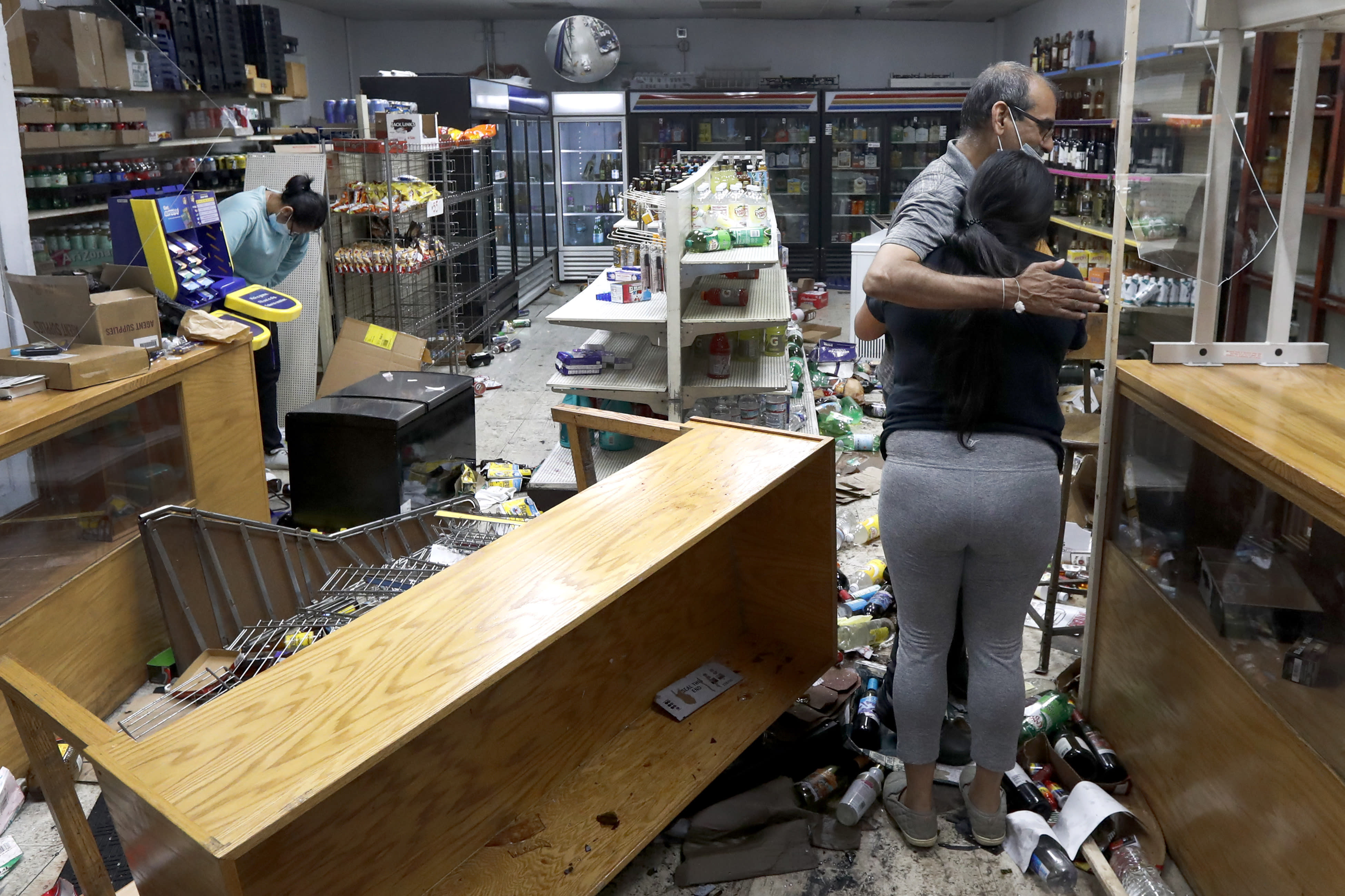 Yogi Dalal hugs his daughter, Jigisha, after she arrived Monday, Aug. 10, 2020 at the family food and liquor store, as his other daughter, Kajal, left, bows her head, after the family business was vandalized in downtown Chicago. (AP Photo/Charles Rex Arbogast, File)