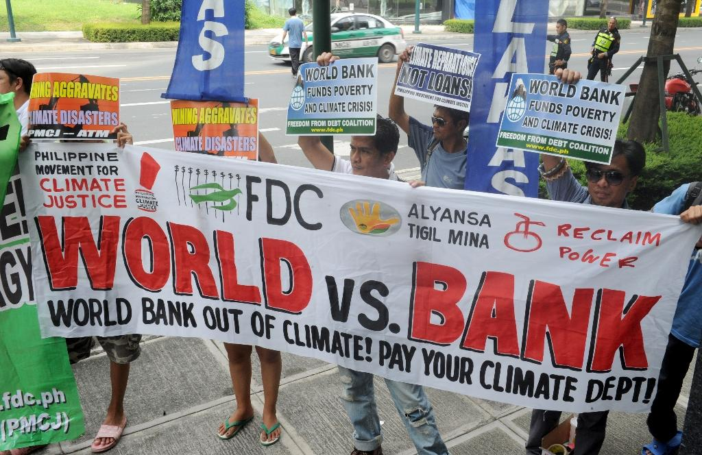 Members of the Freedom from Debt Coalition lead other environmental groups as they protest in front of the World Bank in Bonifacio Global City, Manila on October 10, 2014