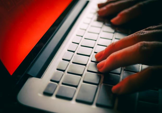 Fingers typing on a laptop keyboard