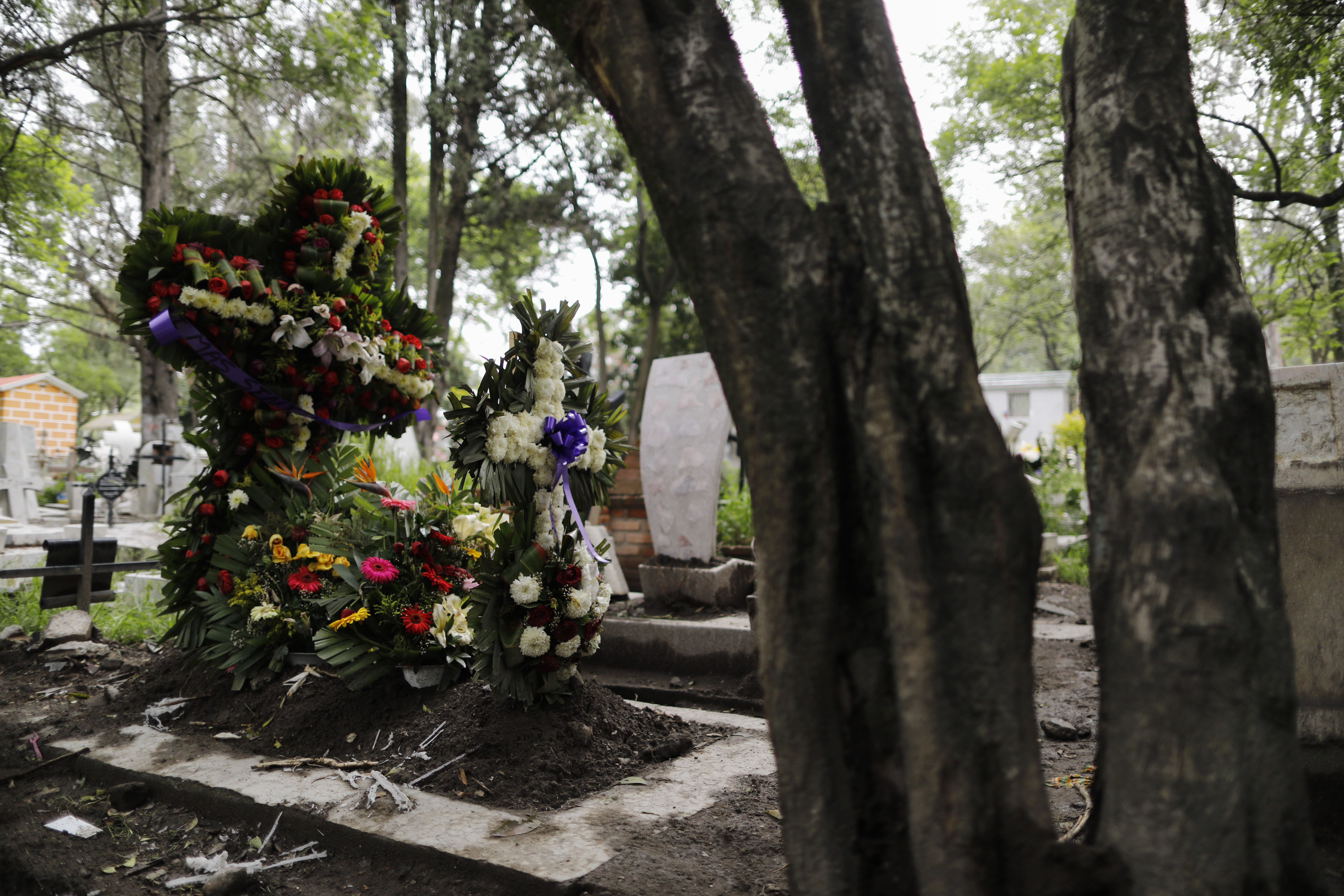 FILE - In this July 27, 2020 file photo, crosses of fresh flowers adorn a new grave at Xilotepec Cemetery amid the new coronavirus pandemic, in Xochimilco, Mexico City. From April 19 to June 30, the capital city saw over 17,800 more deaths than usual. (AP Photo/Rebecca Blackwell, File)
