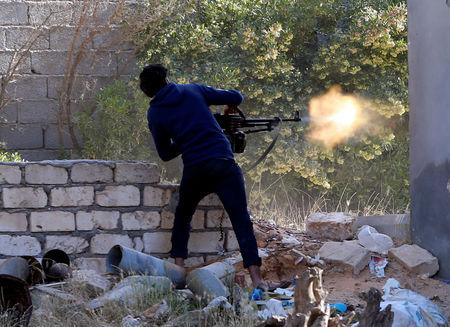 FILE PHOTO - A member of the Libyan internationally recognised government forces fires during a fight with Eastern forces in Ain Zara, Tripoli, Libya April 28, 2019. REUTERS/Ismail Zitouny