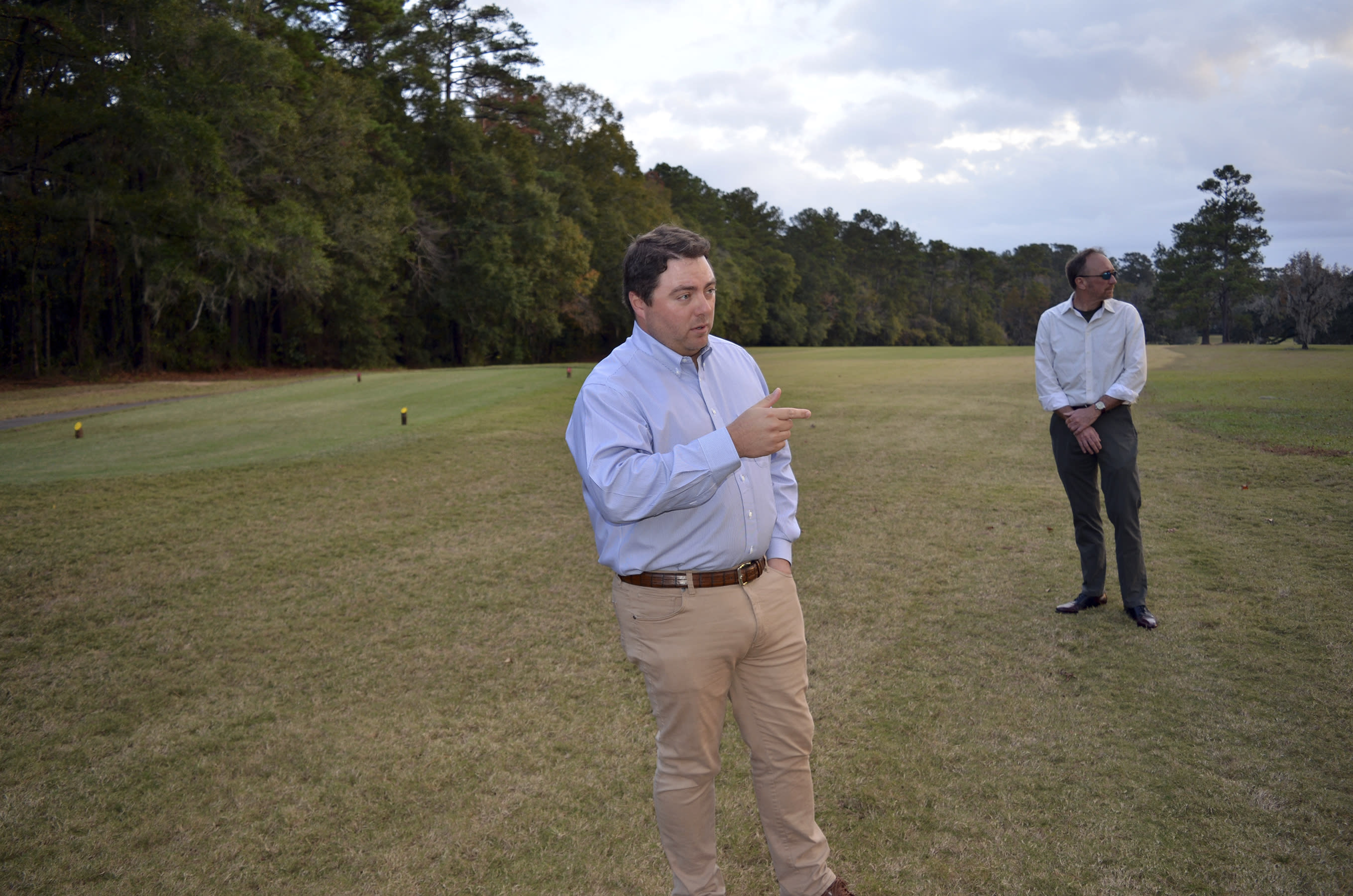 Jay Revell, left, who serves as the historian for the Capital City Country Club, visits the 7th hole of the country club on Dec. 16, 2019, with Jeffrey Shanks, right, an archaeologist with the National Park Service in Tallahassee, Fla. . Revell says the country club's board is considering how to memorialize dozens of slaves buried in an unmarked cemetery near the 7th hole women's tee. The golf course is located on land that was once one a former plantation. (AP Photo/Bobby Caina Calvan)