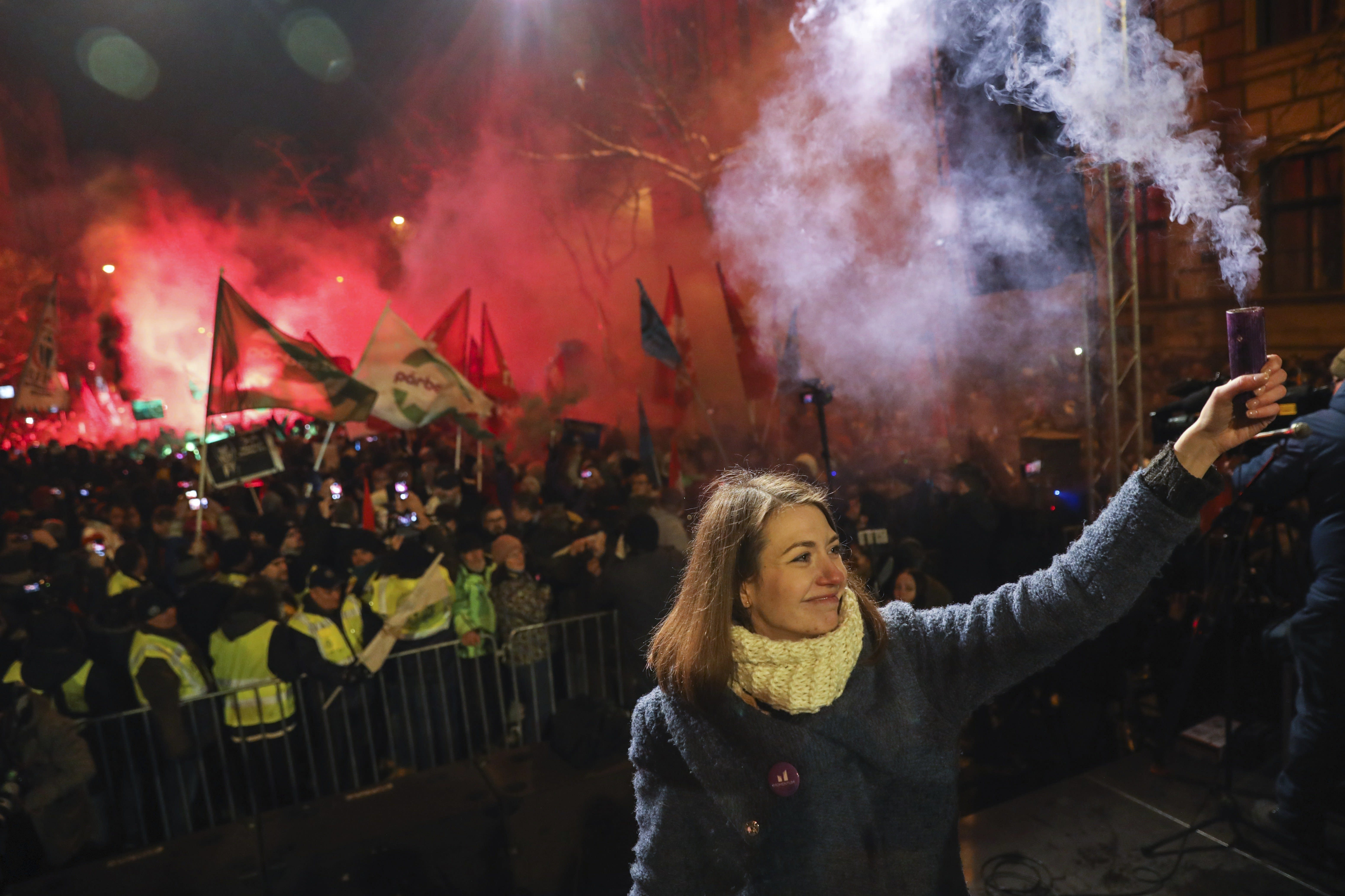 Vice-chairperson of Momentum party Anna Donath holds up a smoke grenade during an anti-government protest in the downtown of Budapest, Hungary, Sunday, Dec. 16, 2018. (Balazs Mohai/MTI via AP)