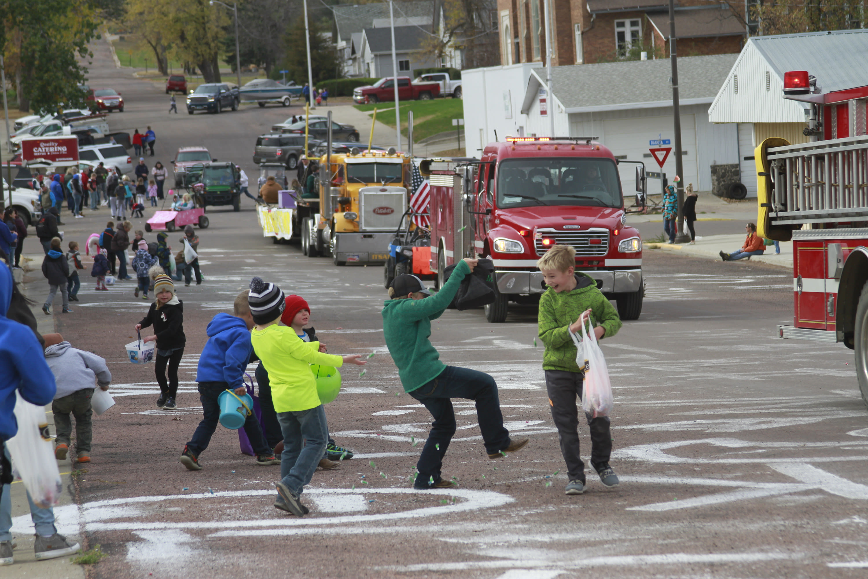 Children scramble for candy during a homecoming parade on Friday Oct. 16, 2020, in Wessington Springs, S.D. The parade had to be postponed due to a coronavirus outbreak that killed five residents of the local nursing home. (AP Photo/Stephen Groves)