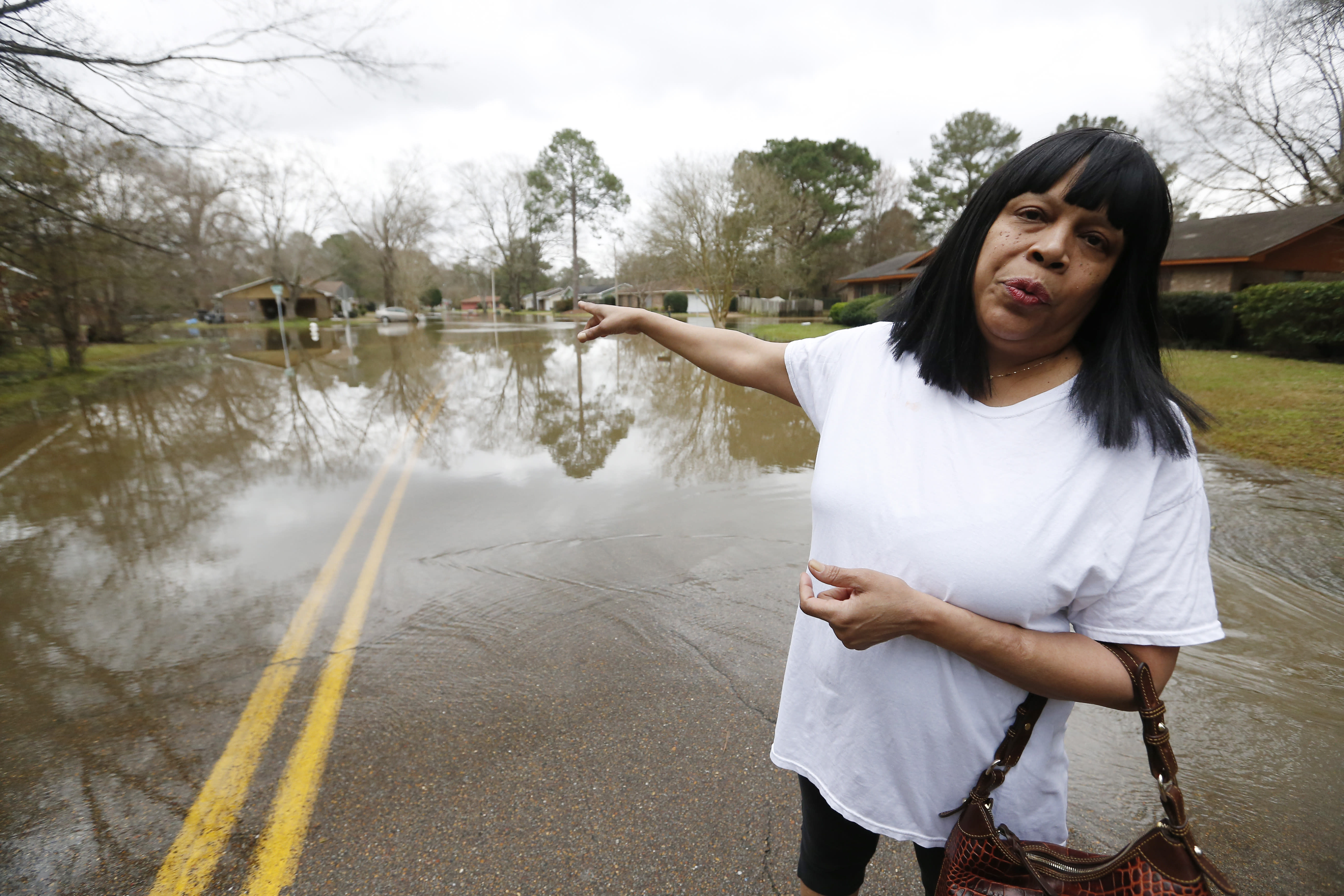 Trina Blackmon, a 28-year resident of northeast Jackson, Miss., wants answers as to why the flooding issues in her neighborhood had not been dealt with, and why she cannot get the city to provide a high water vehicle to take her and others to their homes to so they can inspect the water damage, Tuesday, Feb. 18, 2020. Officials have limited entry to the flooded neighborhoods, warning residents about the current flow and the contamination of the receding waters. (AP Photo/Rogelio V. Solis)