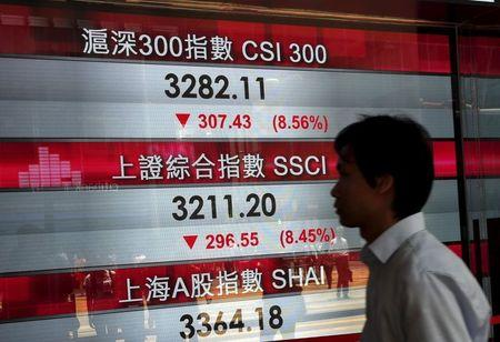 A passerby walks past a panel displaying China stock indexes at the financial Central district in Hong Kong