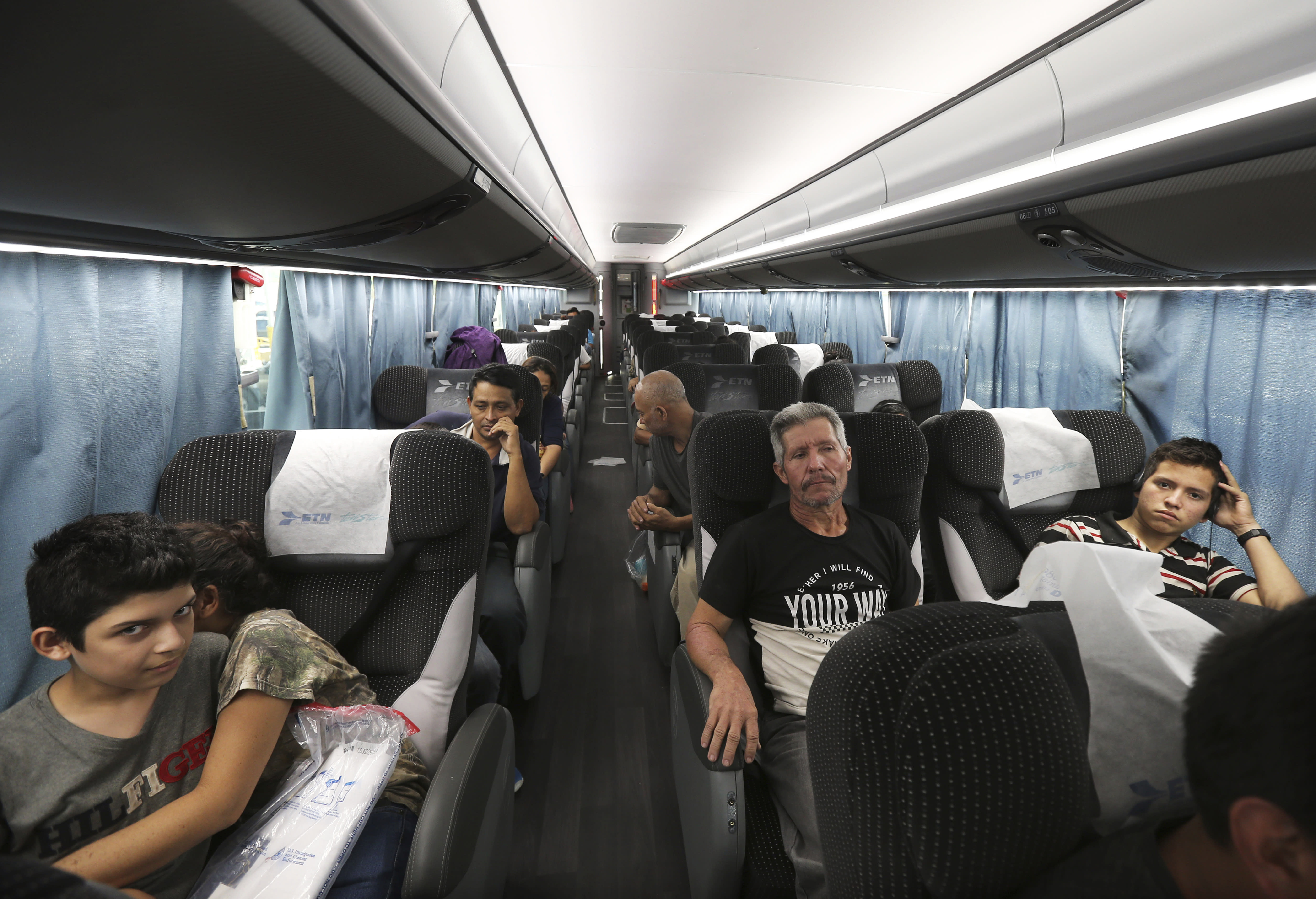 In this July 18, 2019 photo, migrants sit in a bus that will take them and other migrants to Moneterrey, from an immigration center in Nuevo Laredo, Mexico. In Monterrey they found a city where shelters are already overflowing and it quickly became clear that it would be up to them to make do as best as they could. (AP Photo/Marco Ugarte)