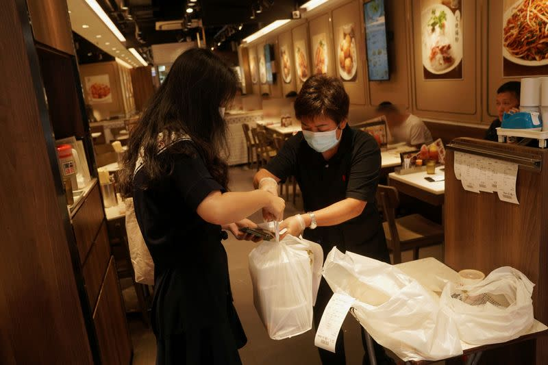 FILE PHOTO: Staff member hands takeaway food to a customer at a restaurant in Hong Kong