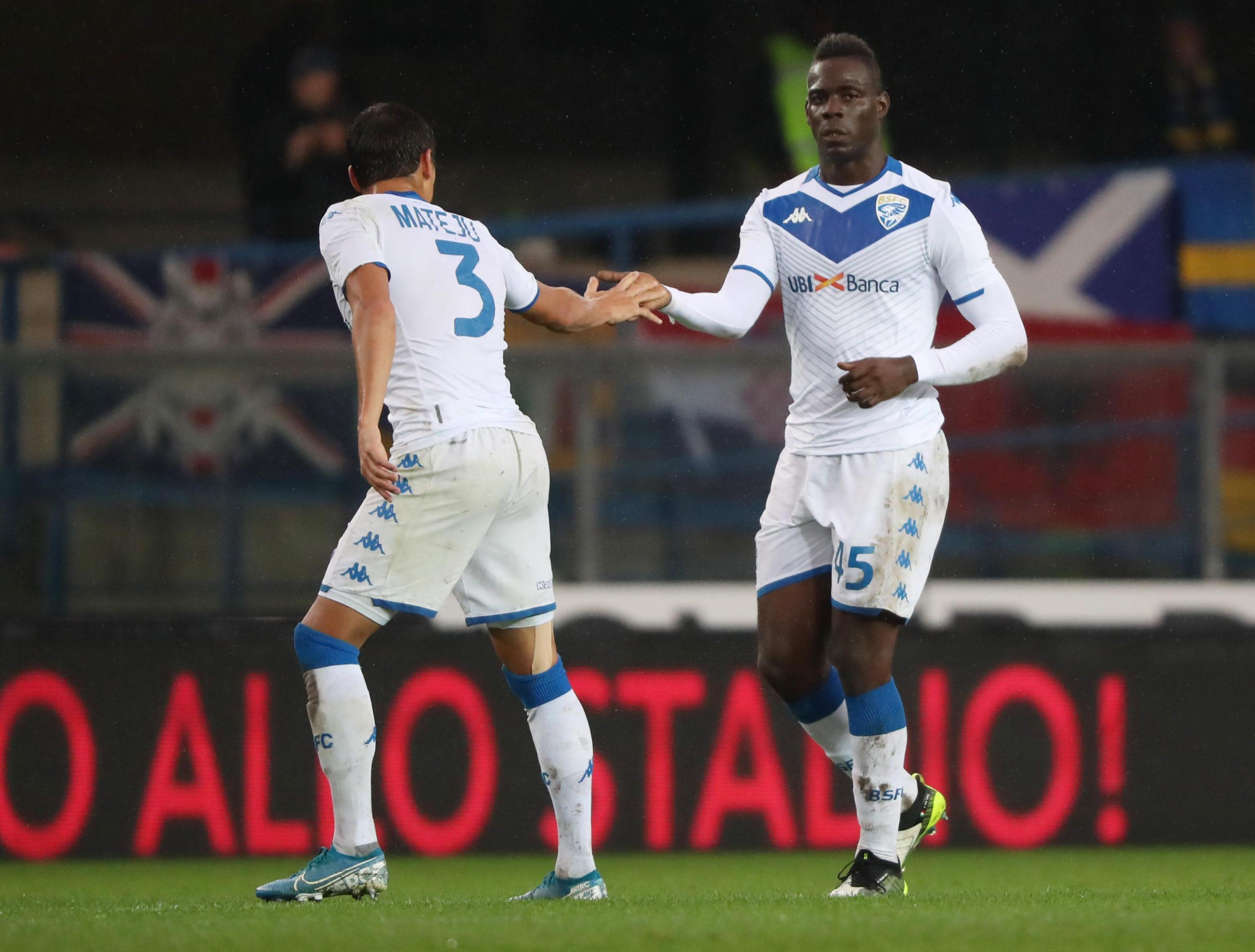 Brescia's Mario Balotelli, right, is congratulated by a teammate after scoring his side's first goal during the Italian Serie A soccer match between Verona and Brescia at the Bentegodi stadium in Verona, Italy, Sunday, Nov. 3, 2019. Verona supporters' racist chants upset the Italian bomber who also kicked the ball to fans in the standings. (Simone Venezia/ANSA via AP)