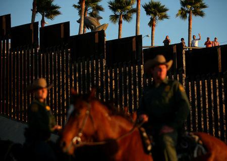 FILE PHOTO: People in Mexico wave at U.S. Border Patrol agents on horseback patrolling the U.S.-Mexico border fence near San Diego, California, U.S., November 10, 2016. REUTERS/Mike Blake/File Photo