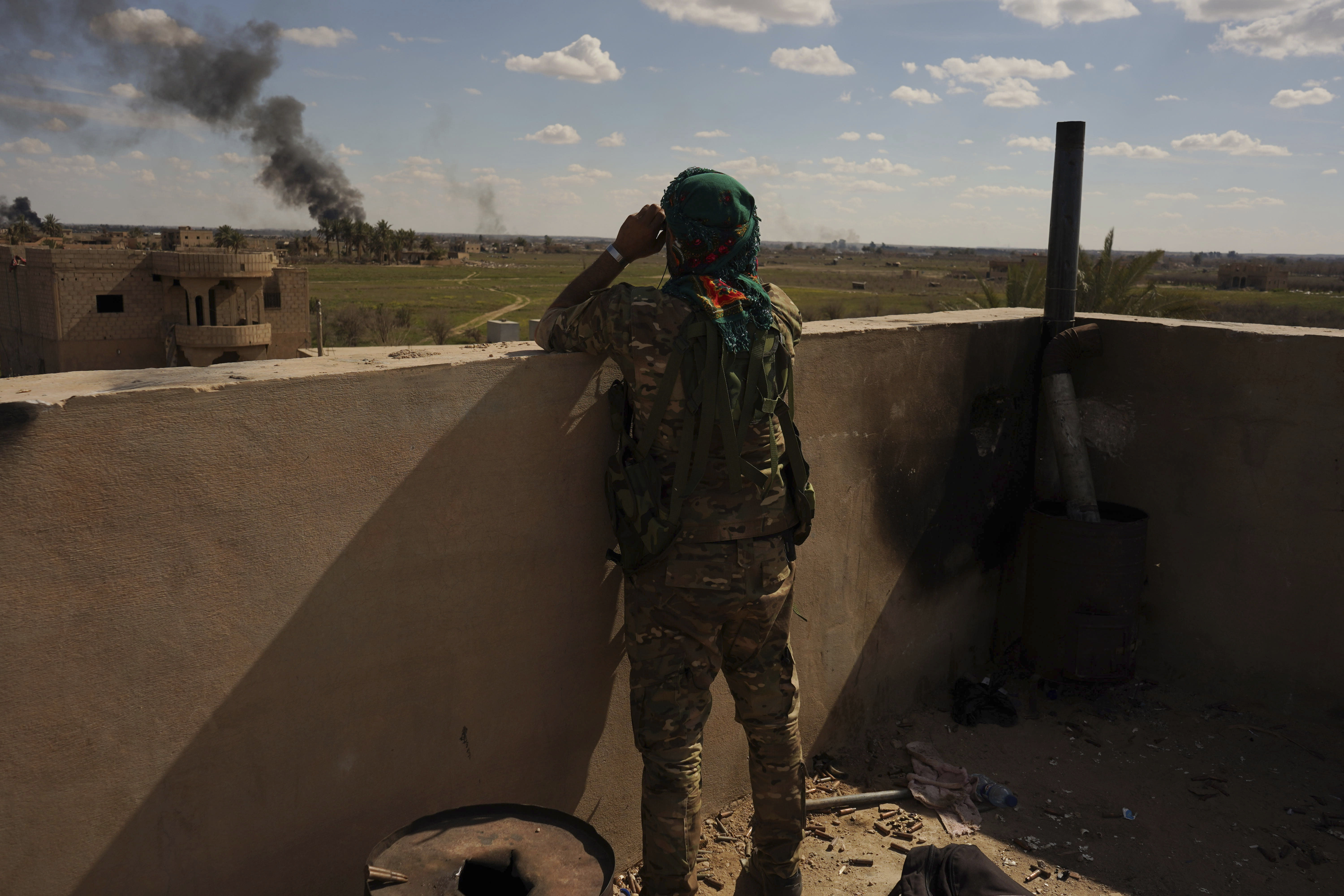 A U.S.-backed Syrian Democratic Forces (SDF) fighter watches black smoke billow from the last small piece of territory held by Islamic State militants as U.S. backed fighters pounded the area with artillery fire and occasional airstrikes in Baghouz, Syria, Sunday, March 3, 2019. (AP Photo/Andrea Rosa)