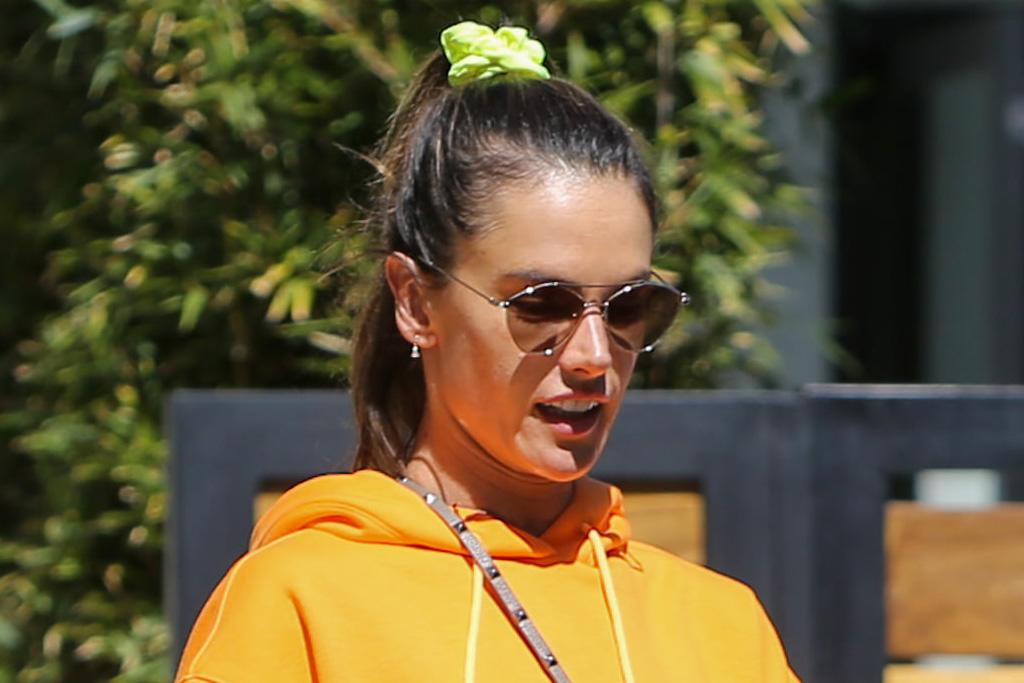 Alessandra Ambrosio Gives the Biker Shorts Trend a Bright Upgrade in a Cropped Hoodie & Glowing Sneakers