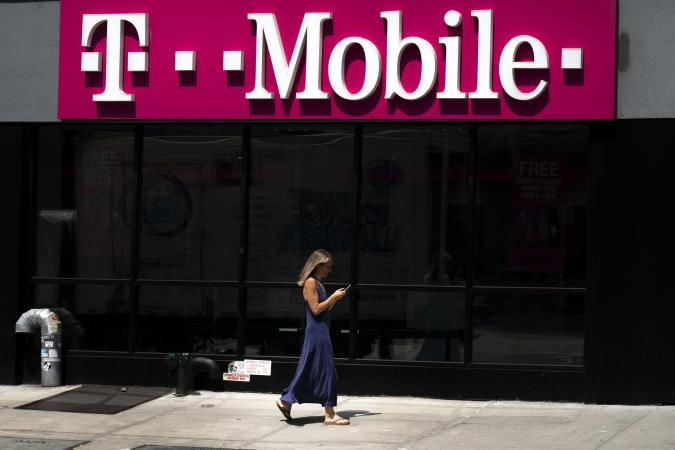 NEW YORK, NY - JULY 26: A woman looks on her phone as she walks past a T-Mobile store on Sixth Avenue in Manhattan on July 26, 2019 in New York City. On Friday, the U.S. Department of Justice approved a merger between T-Mobile and Sprint, the third and fourth largest companies in the U.S. The deal still has one more obstacle to overcome before becoming official; 13 states have filed a lawsuit to block the transaction, citing that reduced competition will harm consumers and drive up prices. (Photo by Drew Angerer/Getty Images)