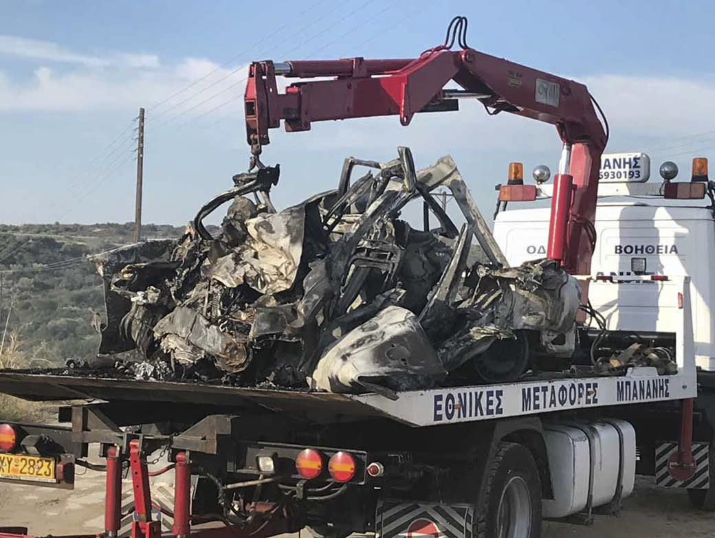 The debris of a car on a crane, following a collision near Greece's northern town of Kavala, Saturday, Oct. 13, 2018. A car carrying migrants collided with a truck in northern Greece on Saturday, killing 11 people, police said. (Proininews.gr via AP)