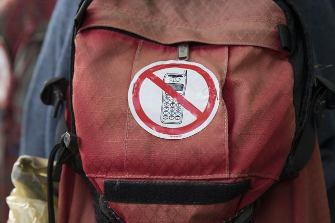 THE HAGUE, NETHERLANDS - SEPTEMBER 9: A protesters carries a backpack with a no-phone sticker during a march against 5G technology on September 9, 2019 in The Hague, Demonstrators are worried about violations of rights concerning, health and radiation, privacy and the environment as tens of thousands of new masts are planned to be installed. Especially long-term effects like cancer, Alzheimer disease and immune illnesses are seen as a threat. (Photo by Michel Porro/Getty Images)