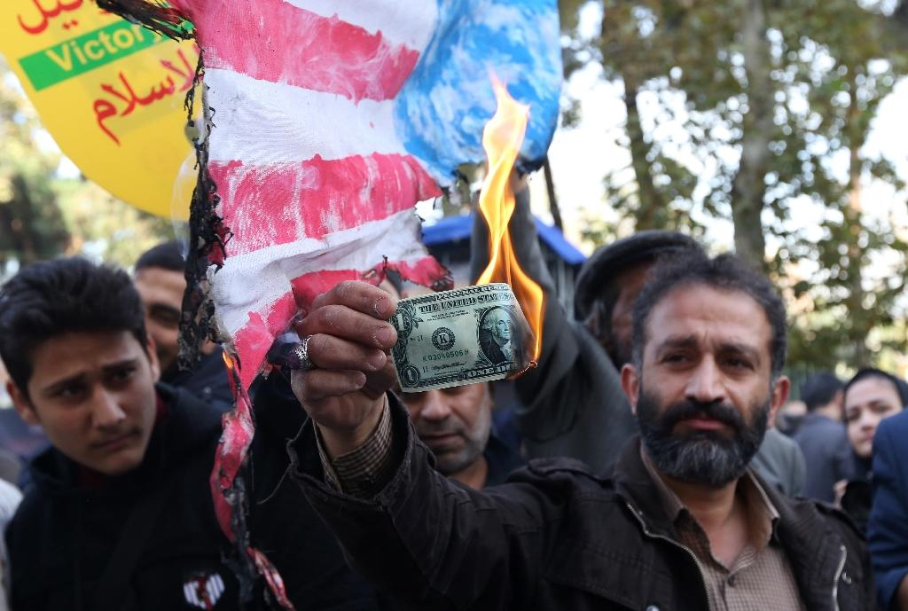 An Iranian protester burns a dollar banknote during a demonstration outside the former US embassy in the Iranian capital Tehran on November 4, 2018 (AFP Photo/ATTA KENARE)