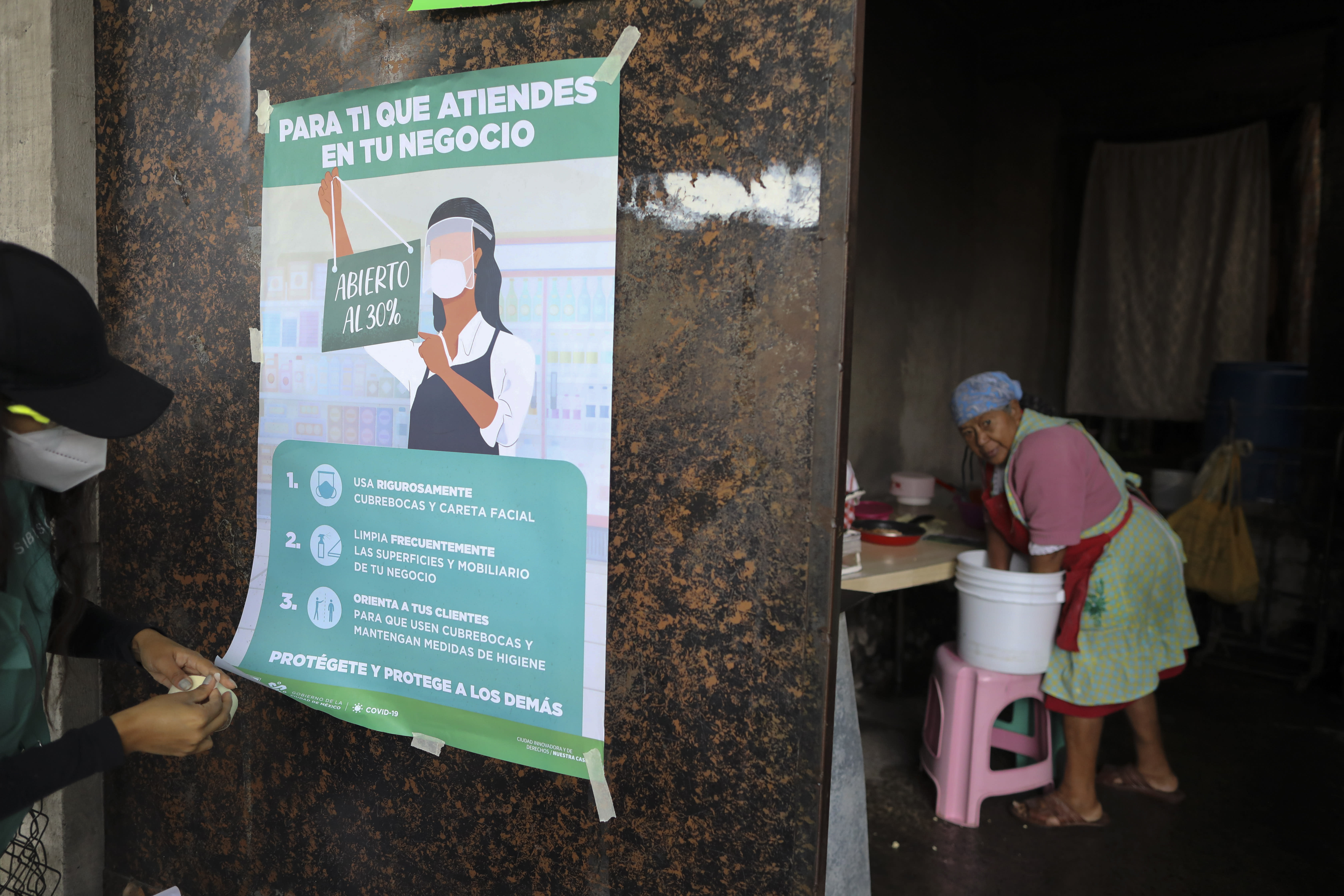 FILE - In this July 21, 2020 file photo, a city health department worker hangs a poster describing the guidelines for businesses operating during the coronavirus pandemic, as a woman prepares to make tortillas inside a small business, in San Mateo Xalpa in the Xochimilco district of Mexico City. Mexican health officials have been holding daily televised news conferences about the pandemic for months, but they have given mixed messages on the necessity of wearing a mask. (AP Photo/Rebecca Blackwell, File)