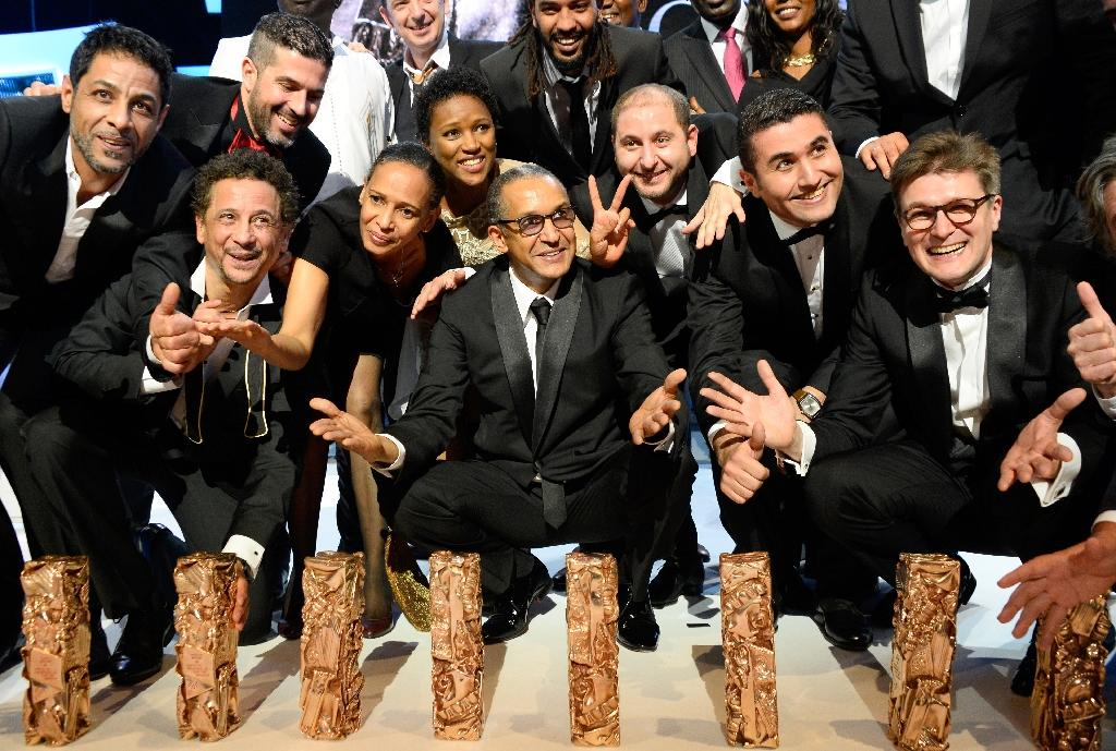 """Mauritanian director Abderrhmane Sissako (C) poses with the trophies he and his crew received after he won the Best Feature Film award for """"Timbuktu"""" at the 40th Cesar Awards ceremony at the Chatelet theatre in Paris on February 20, 2015"""