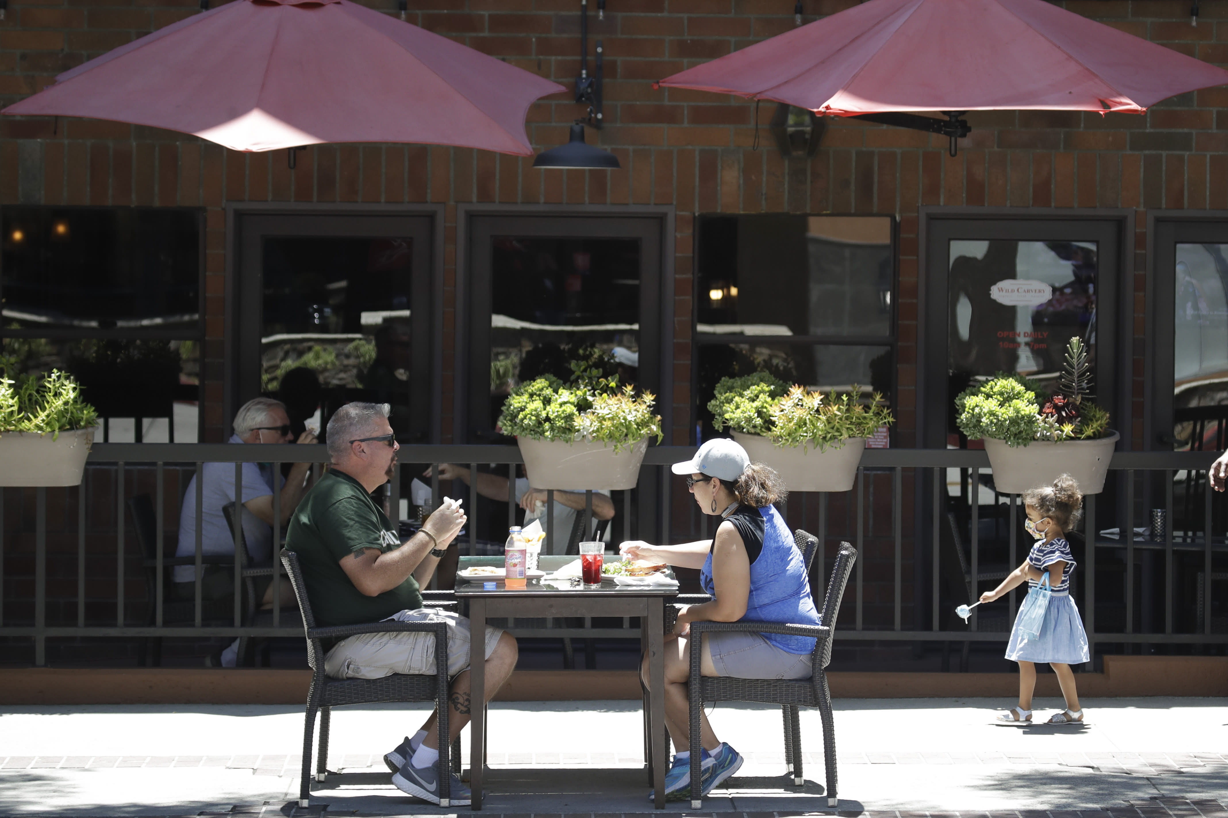 FILE - In this July 18, 2020 file photo patrons eat at table set up on a sidewalk in Burbank, Calif. A steady drop in coronavirus cases across California cleared the way Tuesday, Sept. 22, 2020, for the wider reopening of businesses in nine counties, including much of the Bay Area, the state said. (AP Photo/Marcio Jose Sanchez,File)