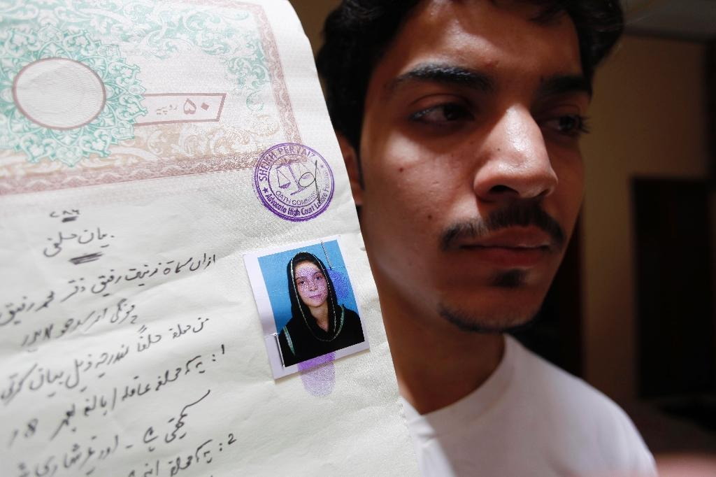 Hassan Khan shows a document with a photograph of his wife Zeenat Bibi, who was burnt alive by her mother, at his residence in Lahore on June 8, 2016 (AFP Photo/)