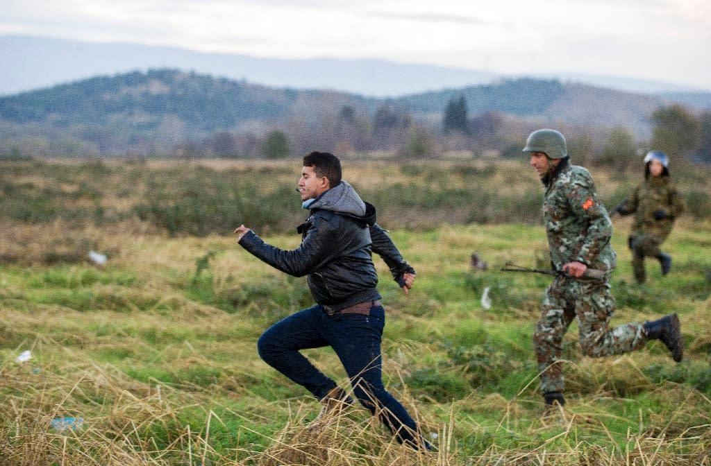 Macedonian police chase a migrant who broke through the border near Gevgelija, at the Greek-Macedonian border, on November 26, 2015