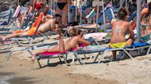 Country's outrage after topless sunbathers told to cover up by police
