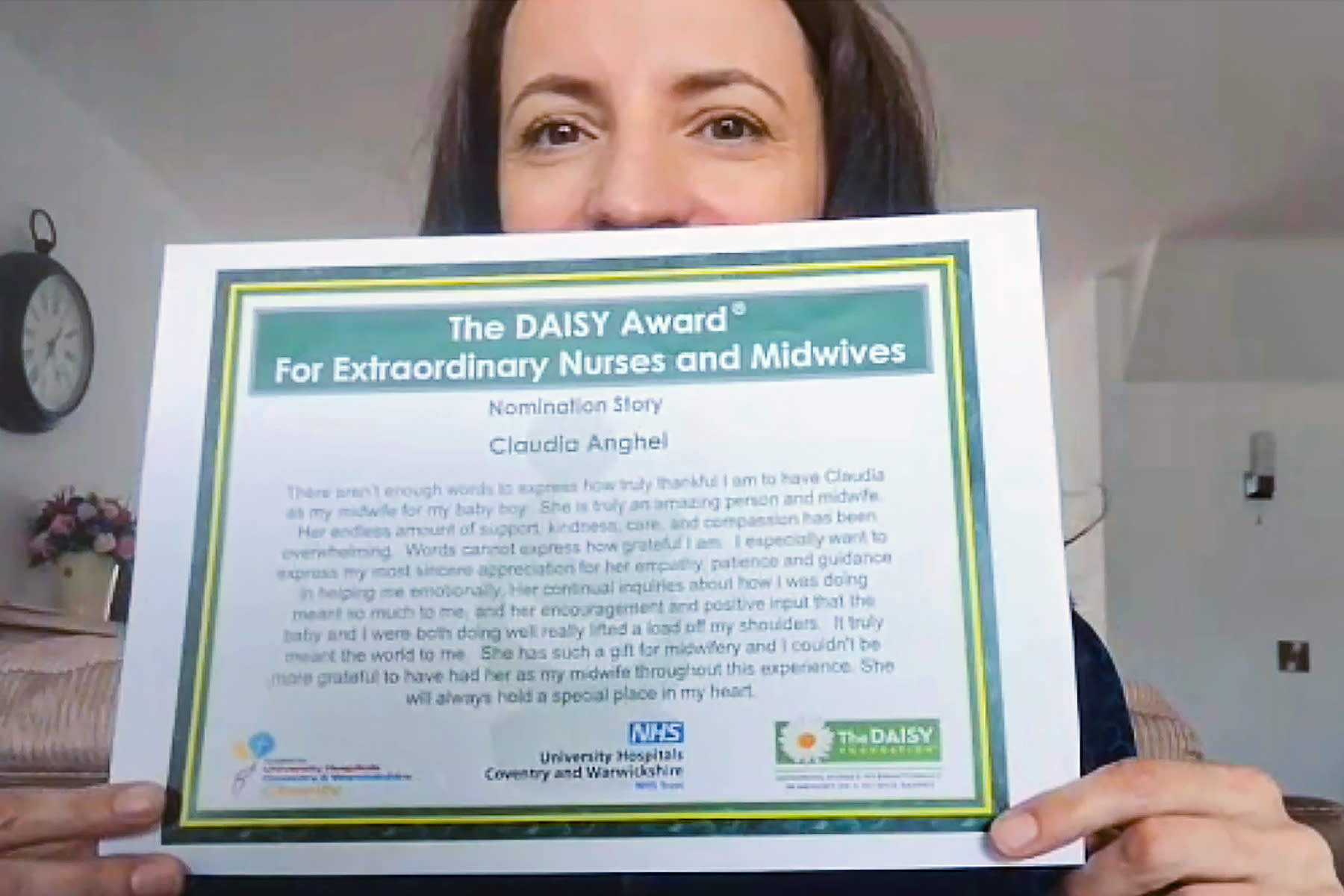 In this image taken from an online video interview with The Associated Press, Claudia Anghel, a Romanian midwife working in England, shows her nomination for the Daisy Award, in Nuneaton, England, Tuesday, July, 28, 2020. Anghel's success story as one of 600,000 Romanians in Britain is at the same time a telling sign of how the deficiencies of her home country's health care system and the bleak prospects for a better future for herself and her family have left huge gaps in Romanian society and its health care system. (AP Photo)