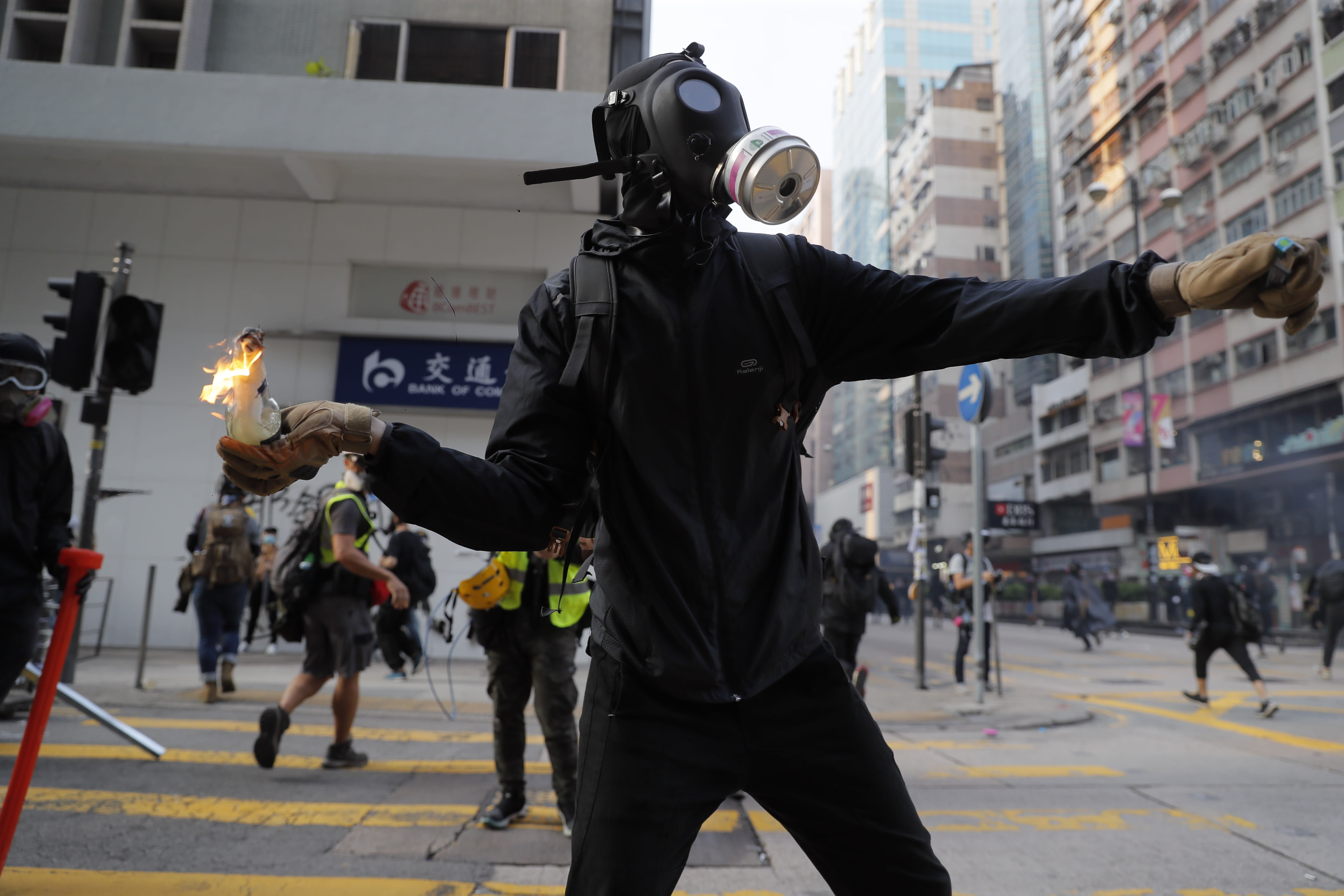 A protester prepares to throw a Molotov cocktail at a police station in Hong Kong, Sunday, Oct. 20, 2019. Hong Kong protesters again flooded streets on Sunday, ignoring a police ban on the rally and demanding the government meet their demands for accountability and political rights. (AP Photo/Kin Cheung)