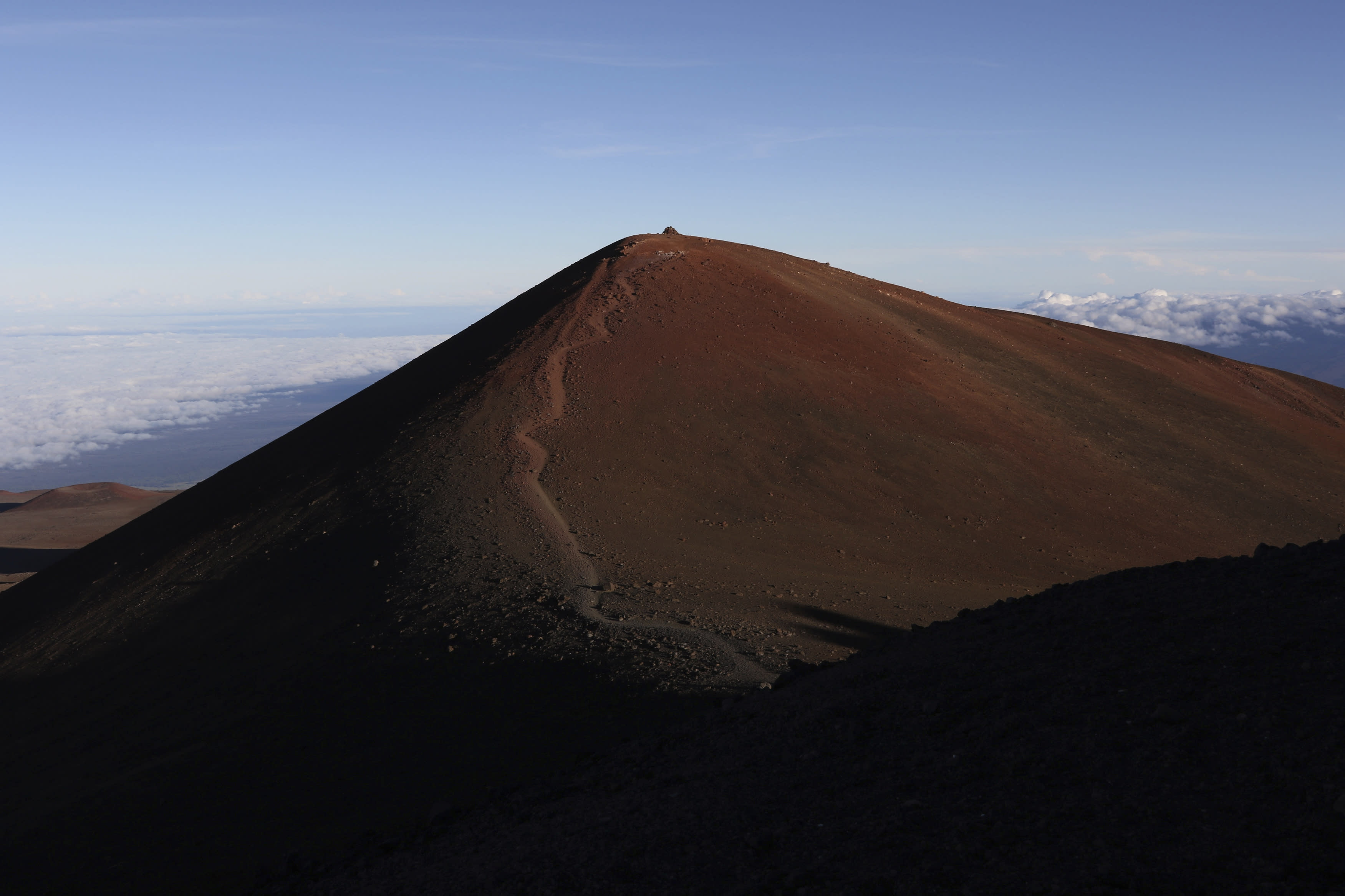 The summit of Hawaii's Mauna Kea is shown on Sunday, July 14, 2019. Hundreds of demonstrators are gathered at the base of Hawaii's tallest mountain to protest the construction of a giant telescope on land that some Native Hawaiians consider sacred. State and local officials will try to close the road to the summit of Mauna Kea Monday morning to allow trucks carrying construction equipment to make their way to the top. Officials say anyone breaking the law will be prosecuted. Protestors have blocked the roadway during previous attempts to begin construction and have been arrested. (AP Photo/Caleb Jones)