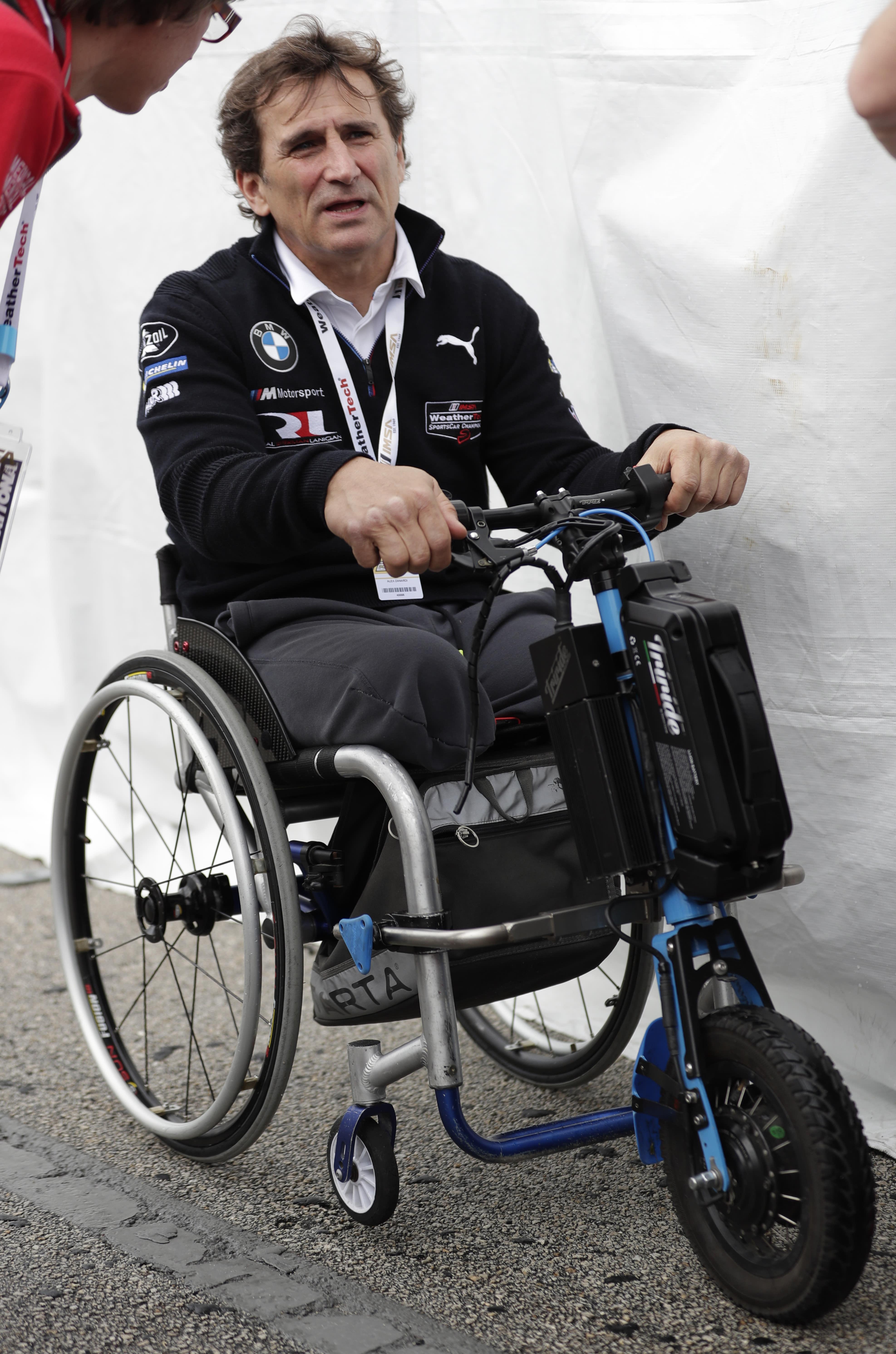 Alex Zanardi talks with visitors outside his pit stall during a practice session for the IMSA 24 hour race at Daytona International Speedway, Thursday, Jan. 24, 2019, in Daytona Beach, Fla. (AP Photo/John Raoux)