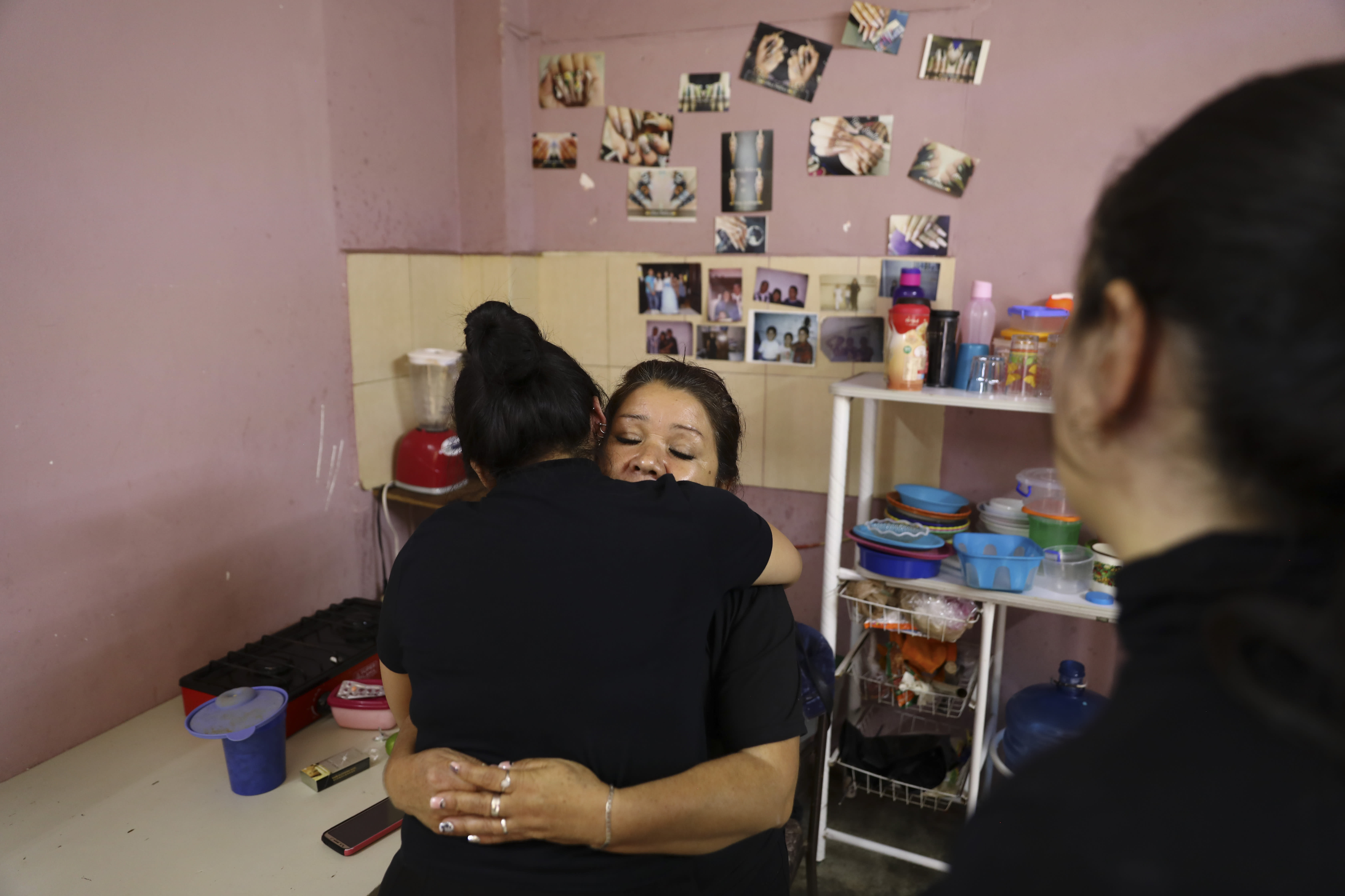 Rosa Alba Santoyo is embraced by a woman giving her condolences the day after she lost three of her adult children in an attack on the drug rehabilitation center where they were being treated, at her home in Irapuato, Mexico, Thursday, July 2, 2020. Gunmen burst into the drug rehabilitation center and opened fire Wednesday, killing 24 people and wounding seven, authorities said. (AP Photo/Eduardo Verdugo)