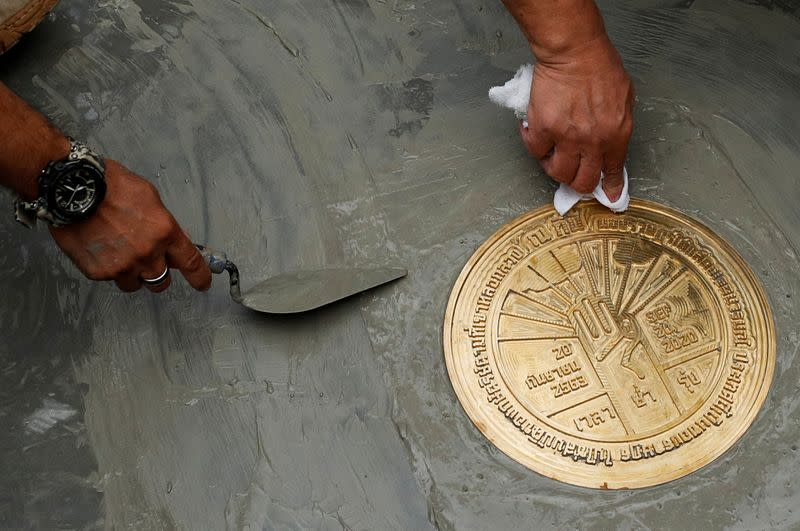 """Student leaders install a plaque declaring """"This country belongs to the people"""" during a mass rally to call for the ouster of Prime Minister Prayuth Chan-ocha and reforms in the monarchy, near the Grand Palace in Bangkok"""