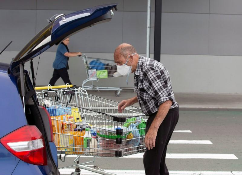 Brian Green, 76, wears a mask as he wheels his supermarket shopping cart to his car outside Pak'nSave supermarket amid the spread of the coronavirus disease (COVID-19) in Christchurch