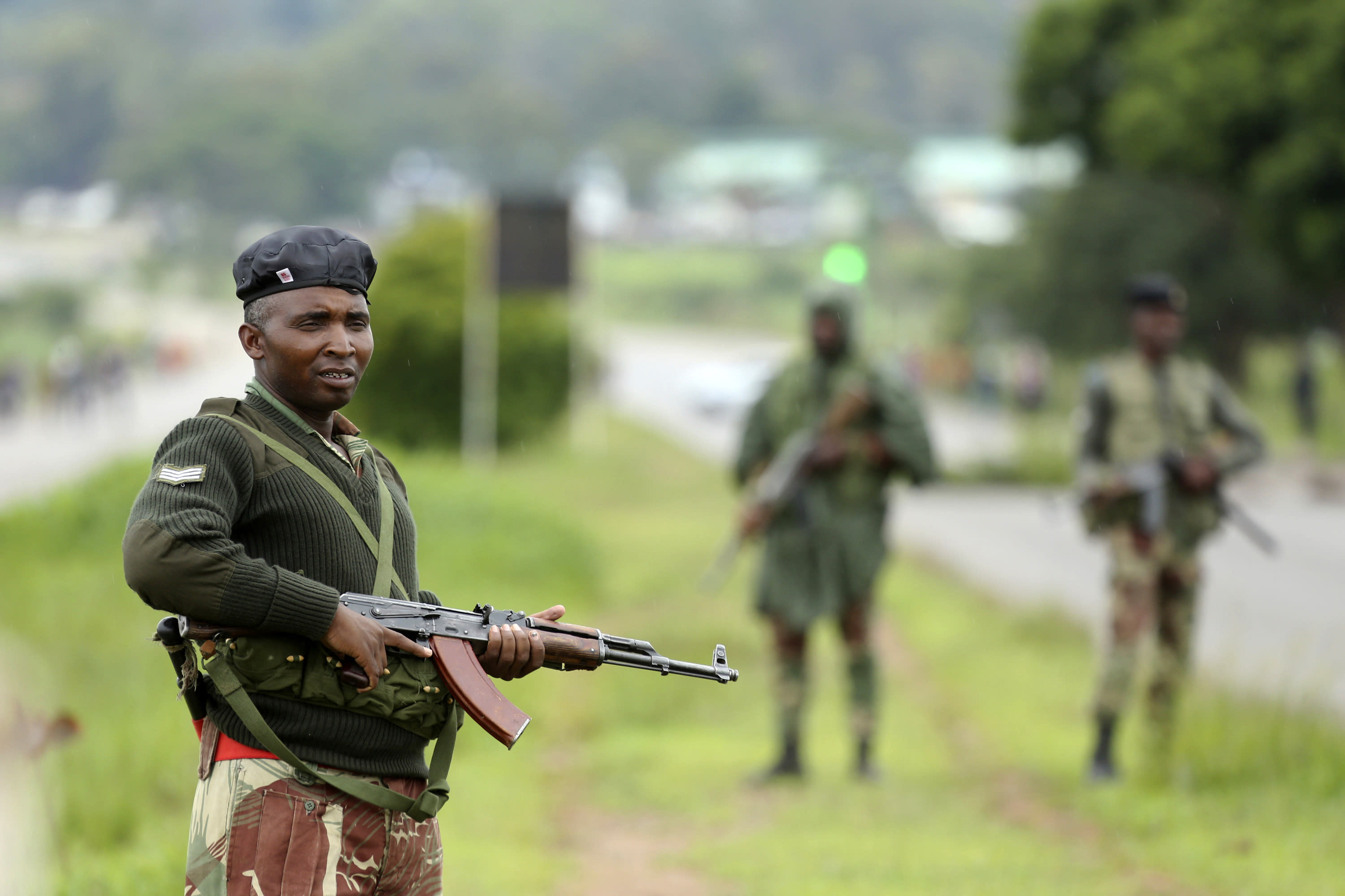 Soldier patrol as protestors gather during a demonstration over the hike in fuel prices in Harare, Zimbabwe, Tuesday, Jan. 15, 2019. A Zimbabwean military helicopter on Tuesday fired tear gas at demonstrators blocking a road and burning tires in the capital on a second day of deadly protests after the government more than doubled the price of fuel in the economically shattered country. (AP Photo/Tsvangirayi Mukwazhi)