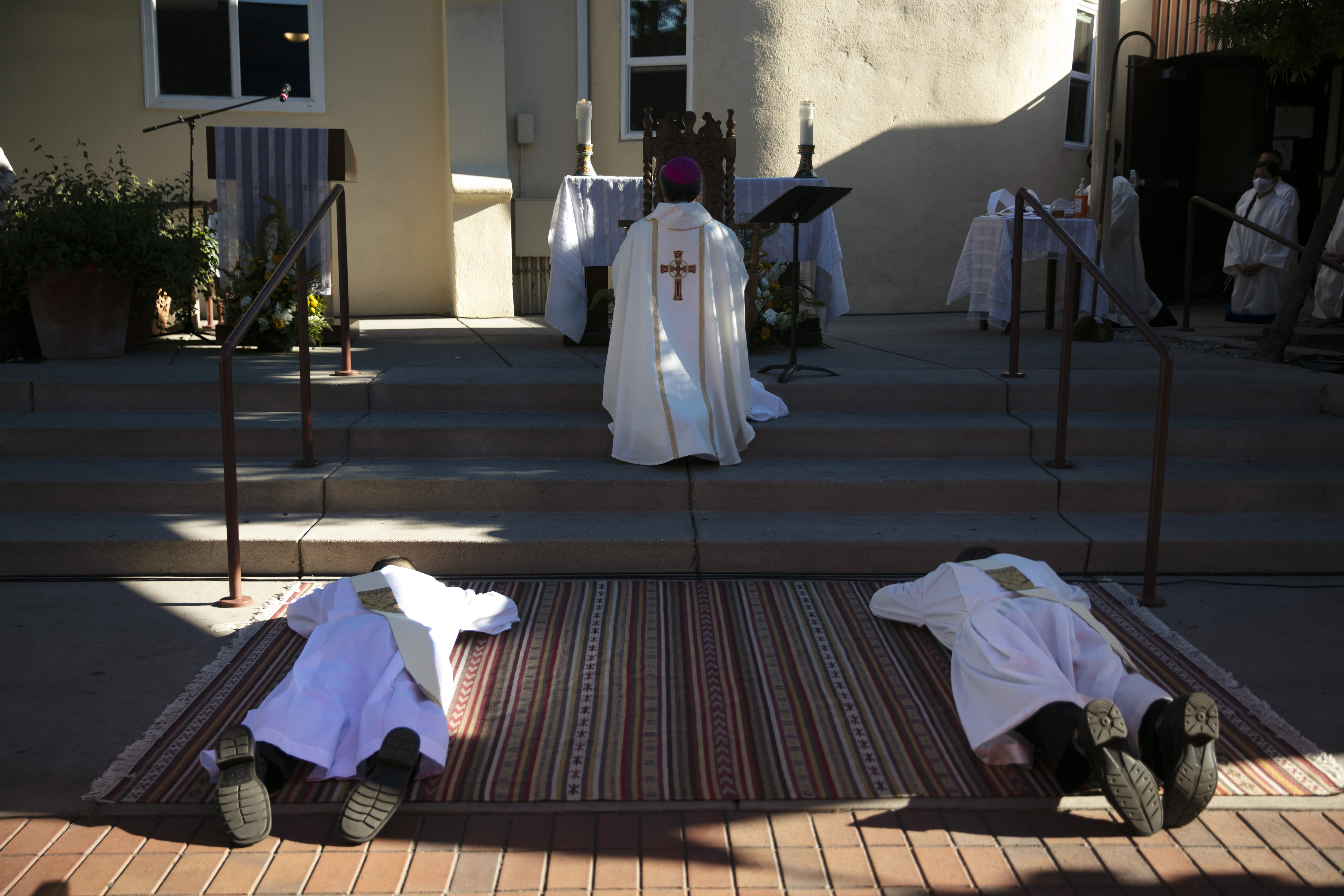 Justin Claravall, bottom left, Gregory Celio lie on a carpet while Bishop Alex Aclan leads a prayer during an ordination ceremony for the new priests at Dolores Mission Church in Los Angeles, Wednesday, July 15, 2020. The ceremony took place outdoors since indoor religious activities have been suspended due to the coronavirus pandemic. (AP Photo/Jae C. Hong)