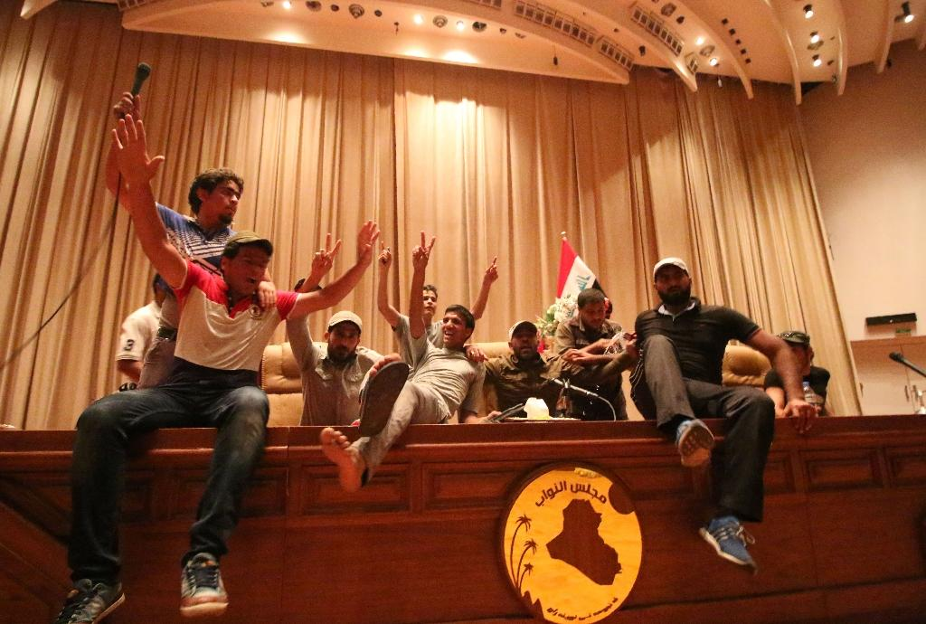 Iraqi protesters flash V-signs inside the parliament building after breaking into Baghdad's heavily fortified Green Zone on April 30, 2016 (AFP Photo/Haidar Mohammed Ali)