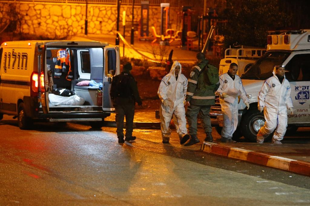 Israeli forensic policemen and security forces walk past an ambulance carrying the body of a Palestinian following a stabbing attack in the Beit Horon settlement in the West Bank, on January 25, 2016 (AFP Photo/Ahmad Gharabli)