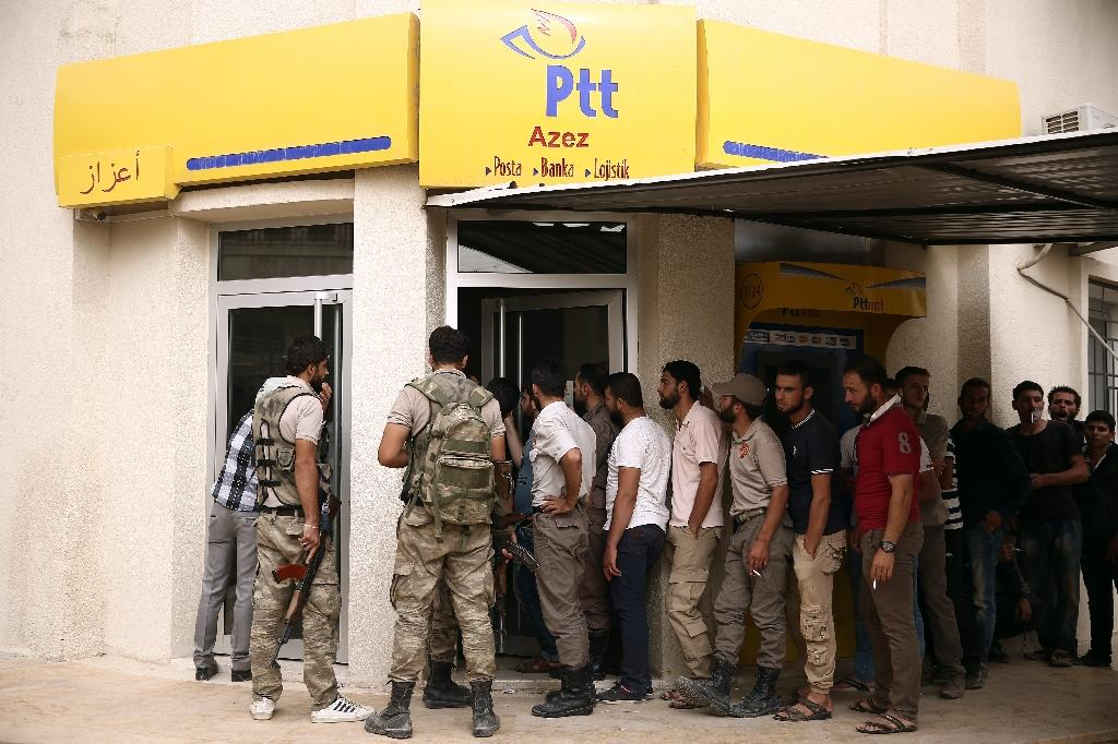 Labourers and rebel fighters stand outside a PTT office, Turkey's state-owned postal service, in the northern Syrian city of Azaz in a rebel-held region of Aleppo province (AFP Photo/Nazeer AL-KHATIB)