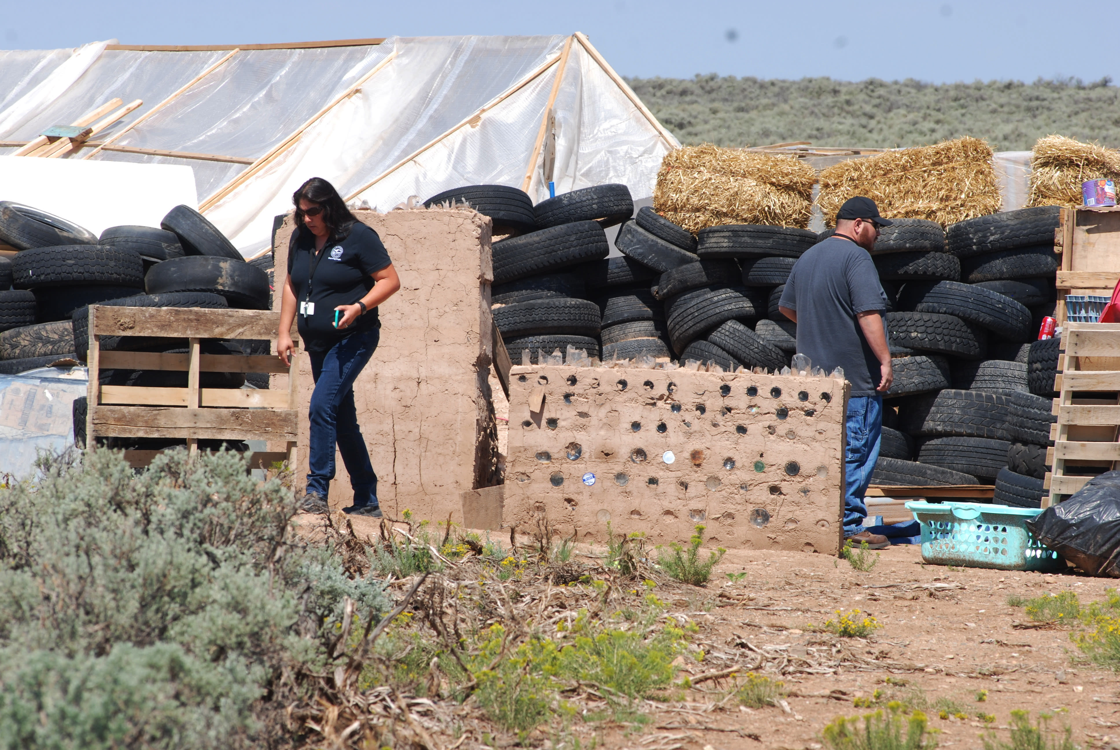 CORRECTS BYLINE TO MORGAN LEE INSTEAD OF LEE MORGAN - Taos County Planning Department officials Rachel Romero, left, and Eric Montoya survey property conditions at a disheveled living compound at Amalia, N.M., on Tuesday, Aug. 7, 2018. A New Mexico sheriff said searchers have found the remains of a boy at the makeshift compound that was raided in search of a missing Georgia child. (AP Photo/Morgan Lee)