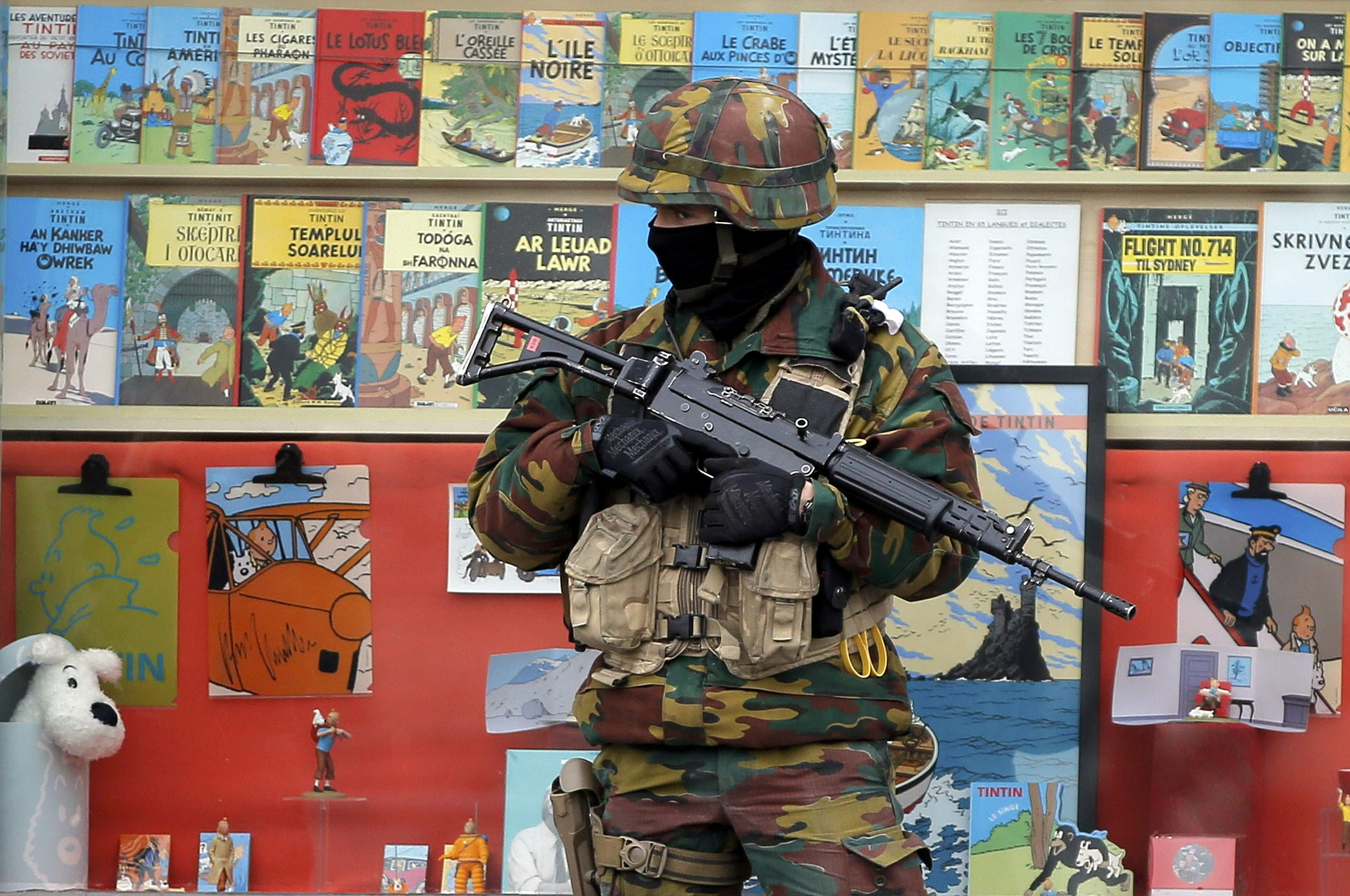 A Belgian soldier stands guard in front of a shop selling Tintin comic books in central Brusselss, Belgium, March 24, 2016. REUTERS/Vincent Kessler TPX IMAGES OF THE DAY