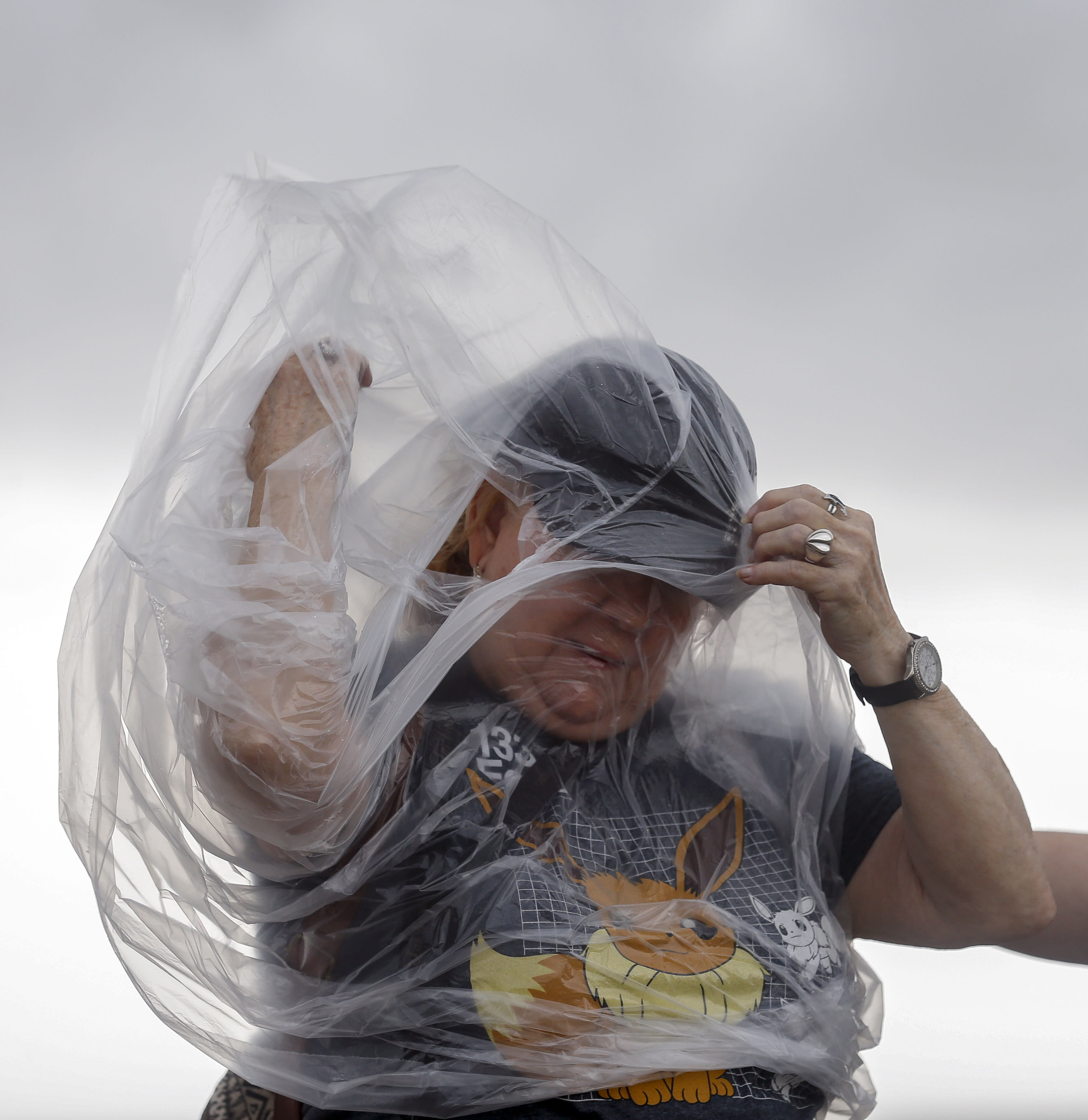 Susan Choate fights the wind to put on a poncho while taking a quick break from being part of the Pokemon Go Fest, which is virtual this year, along Seawall Boulevard on Saturday, July 25, 2020, in Galveston, Texas. Outer bands of Hurricane Hanna are affecting the Houston and Galveston areas. (Godofredo A. Vásquez/Houston Chronicle via AP)