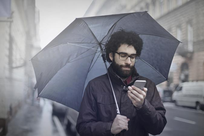 Man is walking on the street with an umbrella and his phone