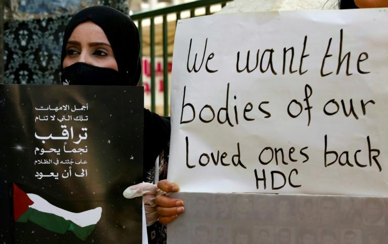 Palestinians hold placards during a demonstration to demand the return of the bodies of relatives who were allegedly involved in attacks and consequently killed by Israeli forces, in the West Bank town of Hebron on Sunday
