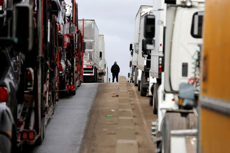 FILE PHOTO: A man stands between trucks waiting in a long queue at border customs control to cross into the U.S, caused by the redeployment of border officers to deal with a surge in migrants, at the Otay border crossing in Tijuana