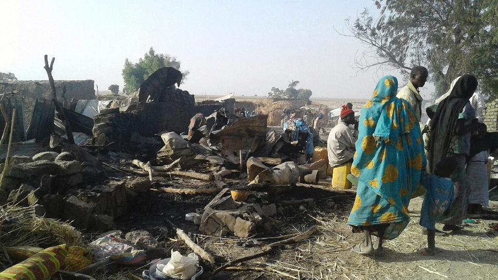 Survivors look at the aftermath of the bombing by the Nigerian air force of a camp for displaced people in Rann, northeast Nigeria, on January 17, 2017 (AFP Photo/)