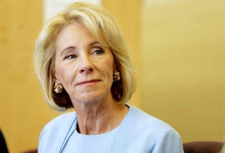 U.S. Secretary of Education Betsy DeVos listens to a presentation during a visit to the Excel Academy public charter school in Washington