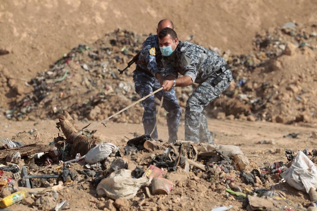 Iraqi police try to pull a body from the mass grave near Hamam al-Alil