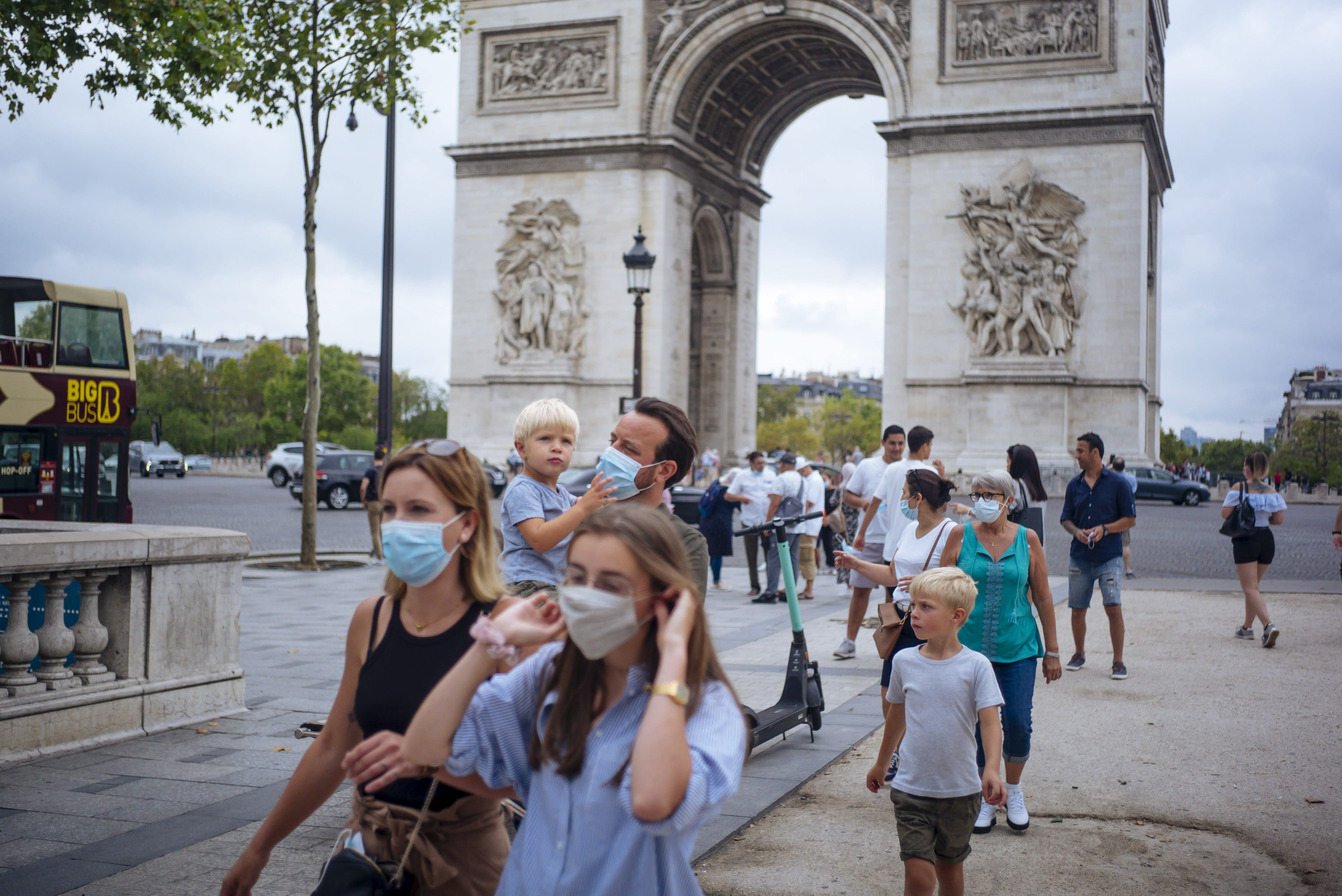 """A family wearing protective face masks walk along on the Champs Elysee avenue, with Arc de Triomphe in background, in Paris, Saturday, Aug. 15, 2020. Paris extended the areas of the city where pedestrians will be obliged to wear masks starting Saturday morning after health officials said that the coronavirus is """"active"""". The Champs-Elysees Avenue and the neighbourhood around the Louvre Museum are among zones where masks will be obligatory. (AP Photo/Kamil Zihnioglu)"""