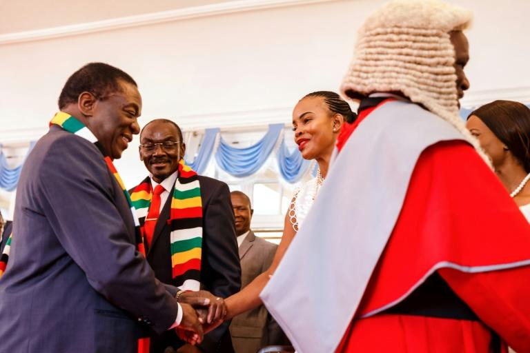 Better times: President Emmerson Mnangagwa, left, shakes hands with Marry Mubawaiafter a swearing-in ceremony for new vice presidents