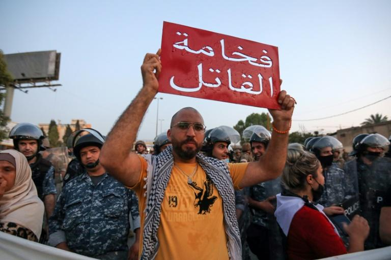 """A Lebanese protester held a sign reading in Arabic """"Your highness the murderer"""", referring to the country's president, during a demonstration earlier this month against the lack of progress in a probe by authorities the Beirut port explosion"""